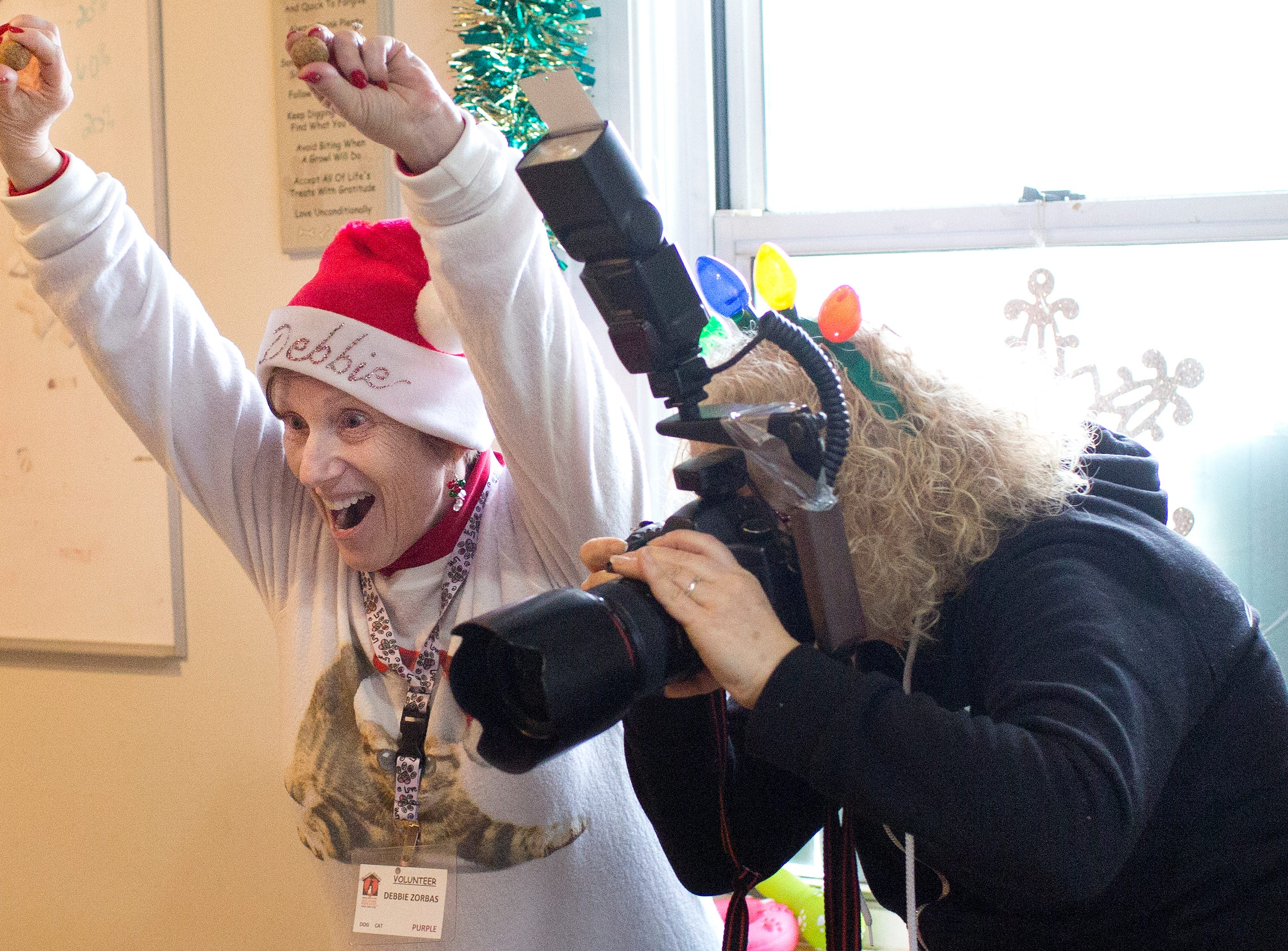 RBARI volunteer Debbie Zorbas (left) tries to catch the attention of pets for photographer Lyn Ofrane during the Santa Paws photo session for pets at the Rampo-Bergen Animal Refuge Inc. in Oakland on Saturday, Dec. 1, 2018. Sponsored by Allstate, all proceeds from the photo sessions go directly towards the care of animals rescued by RBARI.