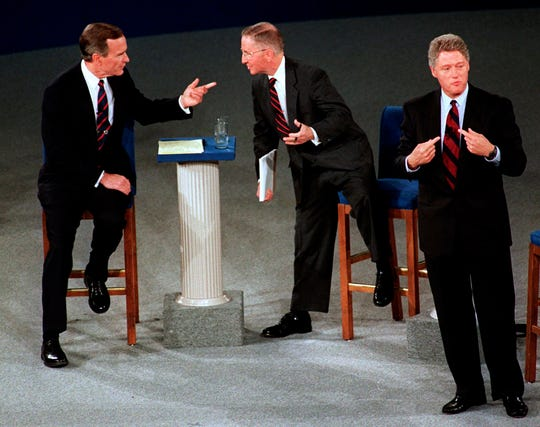 FILE - In this Oct. 15, 1992, file photo, President George H.W. Bush, left, talks with independent candidate Ross Perot as Democratic candidate Bill Clinton stands aside at the end of their second presidential debate in Richmond, Va. Bush died at the age of 94 on Friday, Nov. 30, 2018, about eight months after the death of his wife, Barbara Bush