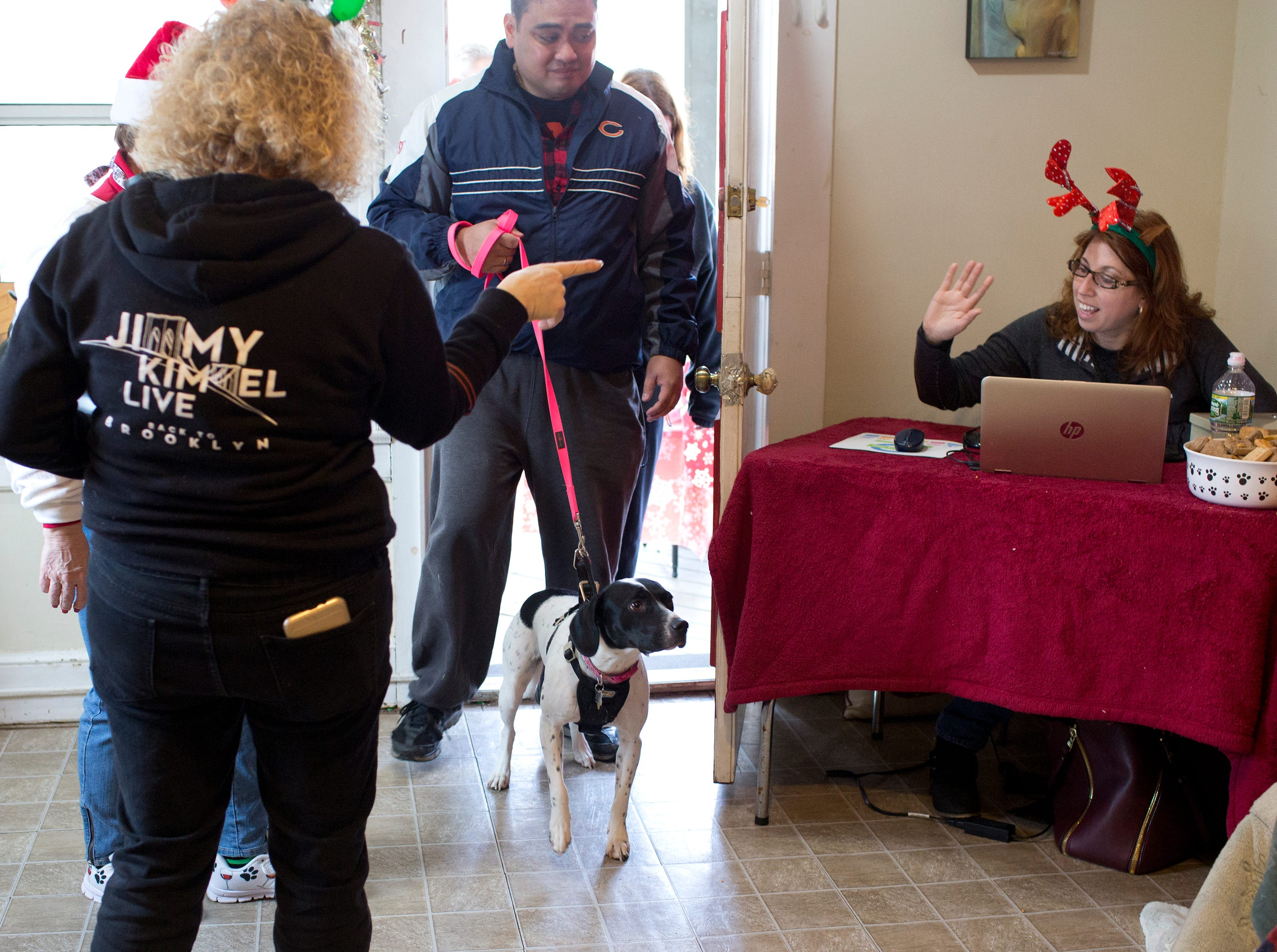 Roxy, a one year old dog, enters tentatively with her owners Frank and Beth Reyes from Hawthorne as volunteer Kristie Mosley (right) waves during the Santa Paws photo session for pets at the Rampo-Bergen Animal Refuge Inc. in Oakland on Saturday, Dec. 1, 2018. Sponsored by Allstate, all proceeds from the photo sessions go directly towards the care of animals rescued by RBARI.