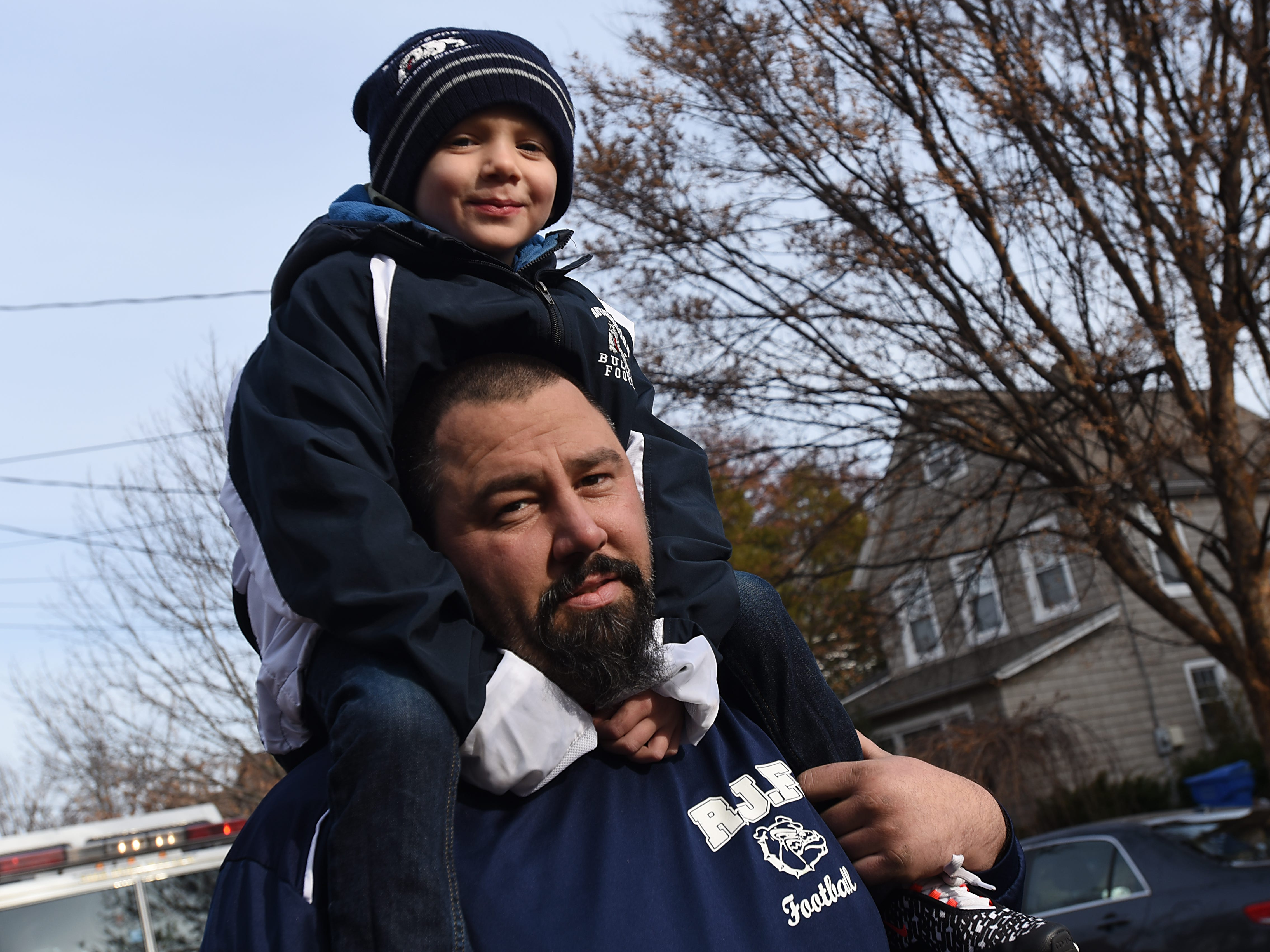 Parker Garofalo, five, rides on Rudy Garofalo's shoulders during the Rutherford Football parade in Rutherford on Saturday December 1, 2018.