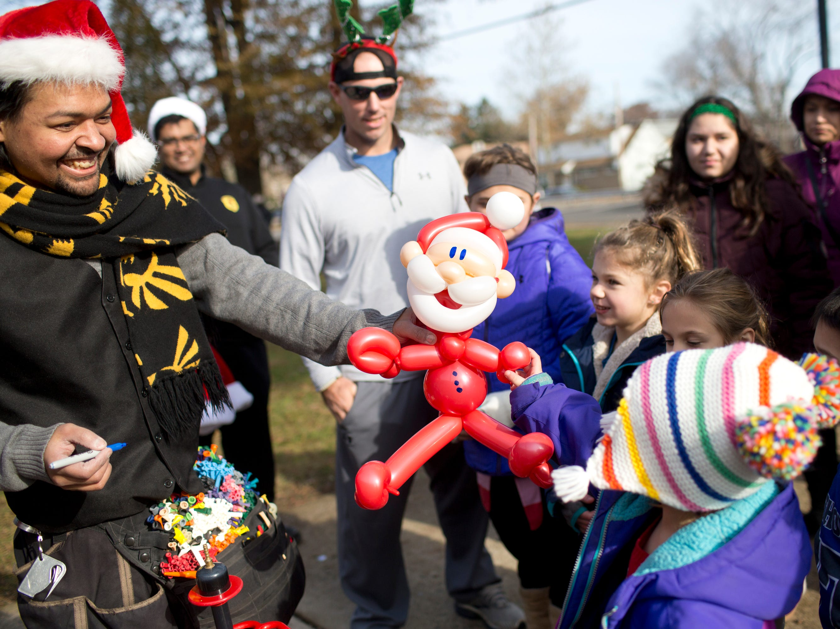 Will Sanchez with Magnificent Entertainment creates a Santa Claus out of balloons for Hailee Bosgra, 4, as her dad Dan Bosgra watches after the 33rd Annual Santa Parade in Hawthorne on Saturday, Dec. 1, 2018.
