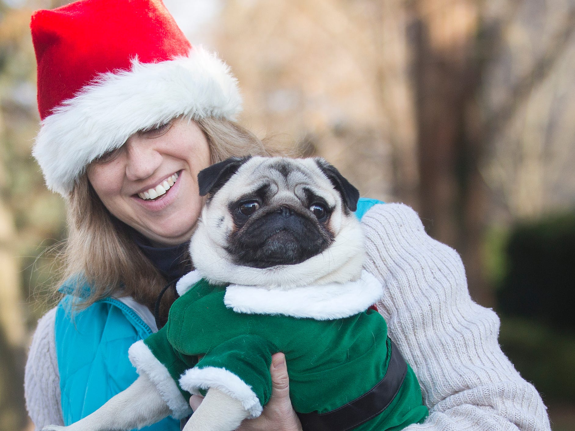 Brenda Van Der Eems holds her Pug dog Ernie, 3, ready to watch the 33rd Annual Santa Parade in Hawthorne on Saturday, Dec. 1, 2018.