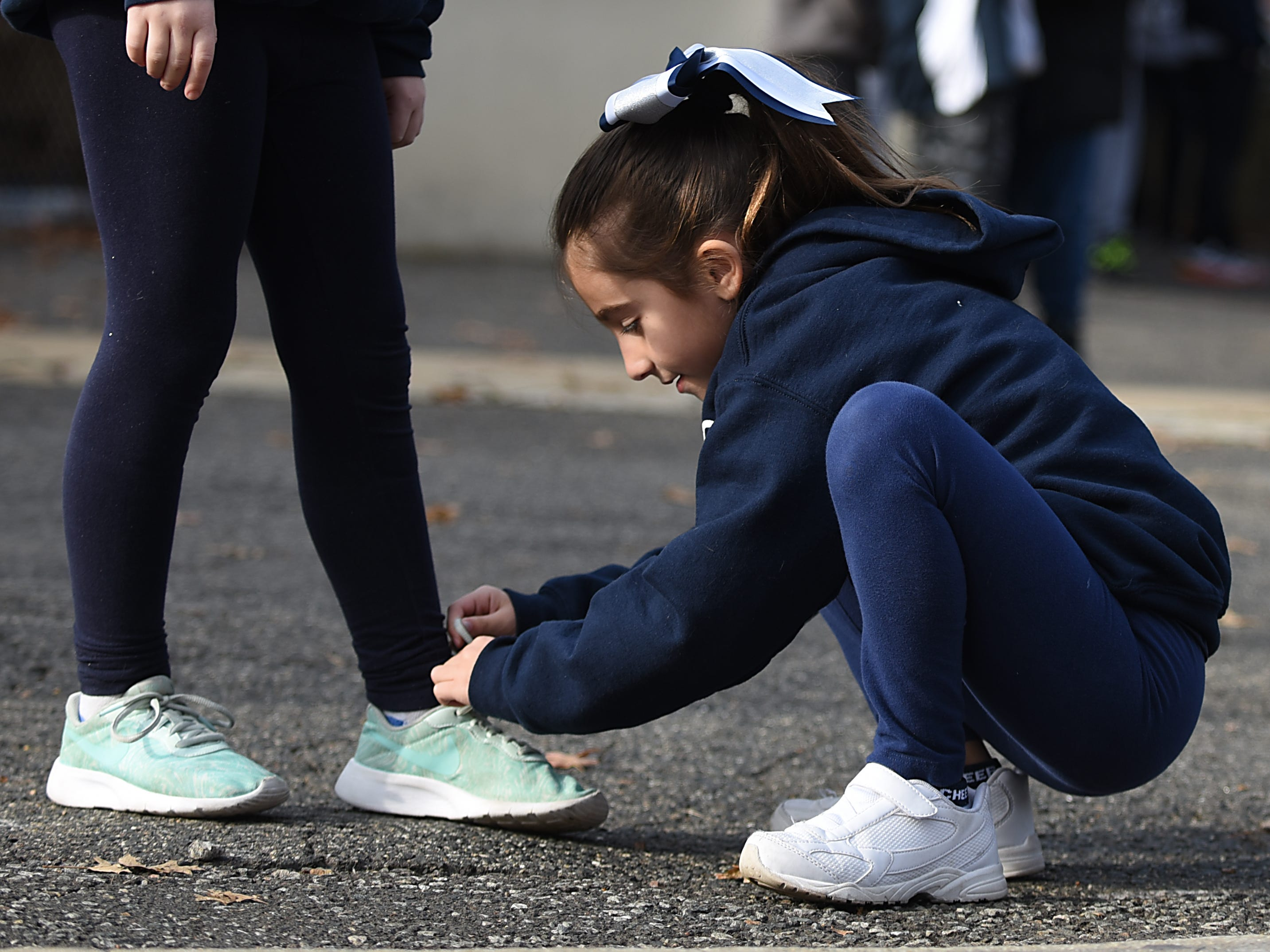 Giuliana Centrello, eight years old, helps her fellow cheerleader tie her shoe prior to the start of the Rutherford Football parade in Rutherford on Saturday December 1, 2018.
