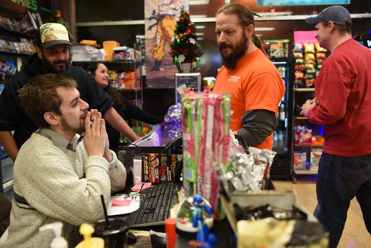 (From left) Sean Abline, Emerito Rivera - Owner and Cinithia Rivera - Owner help customers Ian Dampman and Chris Flammer at Level 1 Games in Pompton Plains on Friday November 30, 2018.