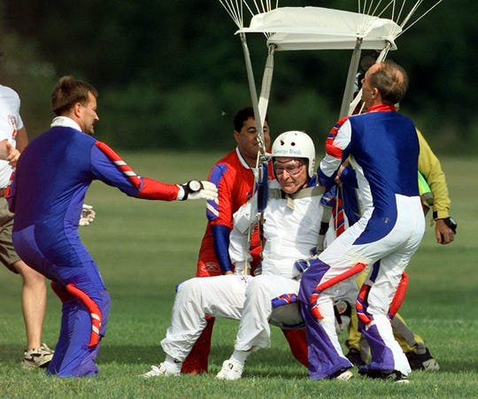 Former President George H.W. Bush, center, is helped as he lands after his parachute jump Wednesday, June 9, 1999, in College Station, Texas. Bush made the jump as part of his 75th birthday celebration.