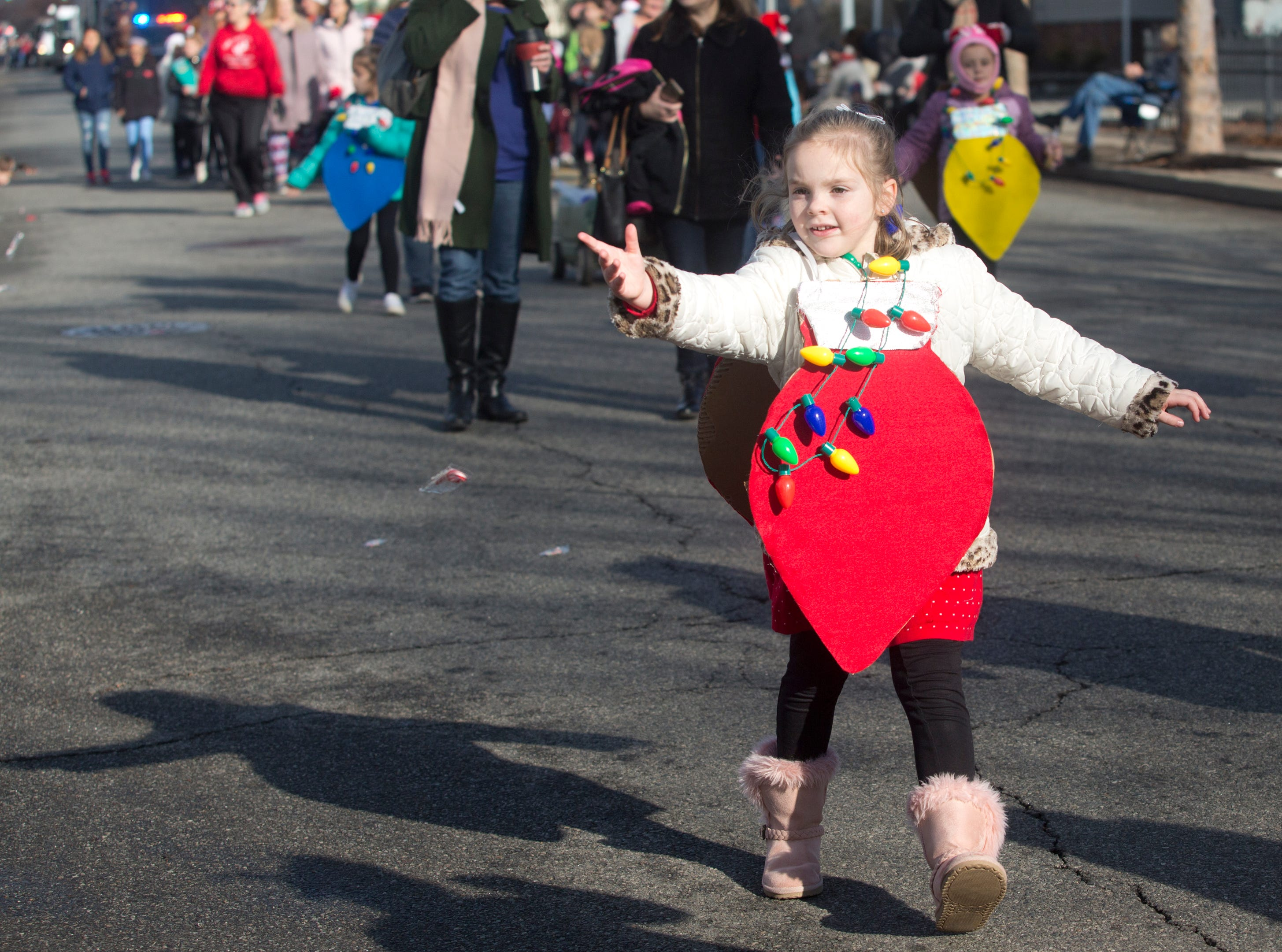 Zoe Mogen with Daisy Troop 97293 throws candy to parade goers during the 33rd Annual Santa Parade in Hawthorne on Saturday, Dec. 1, 2018.