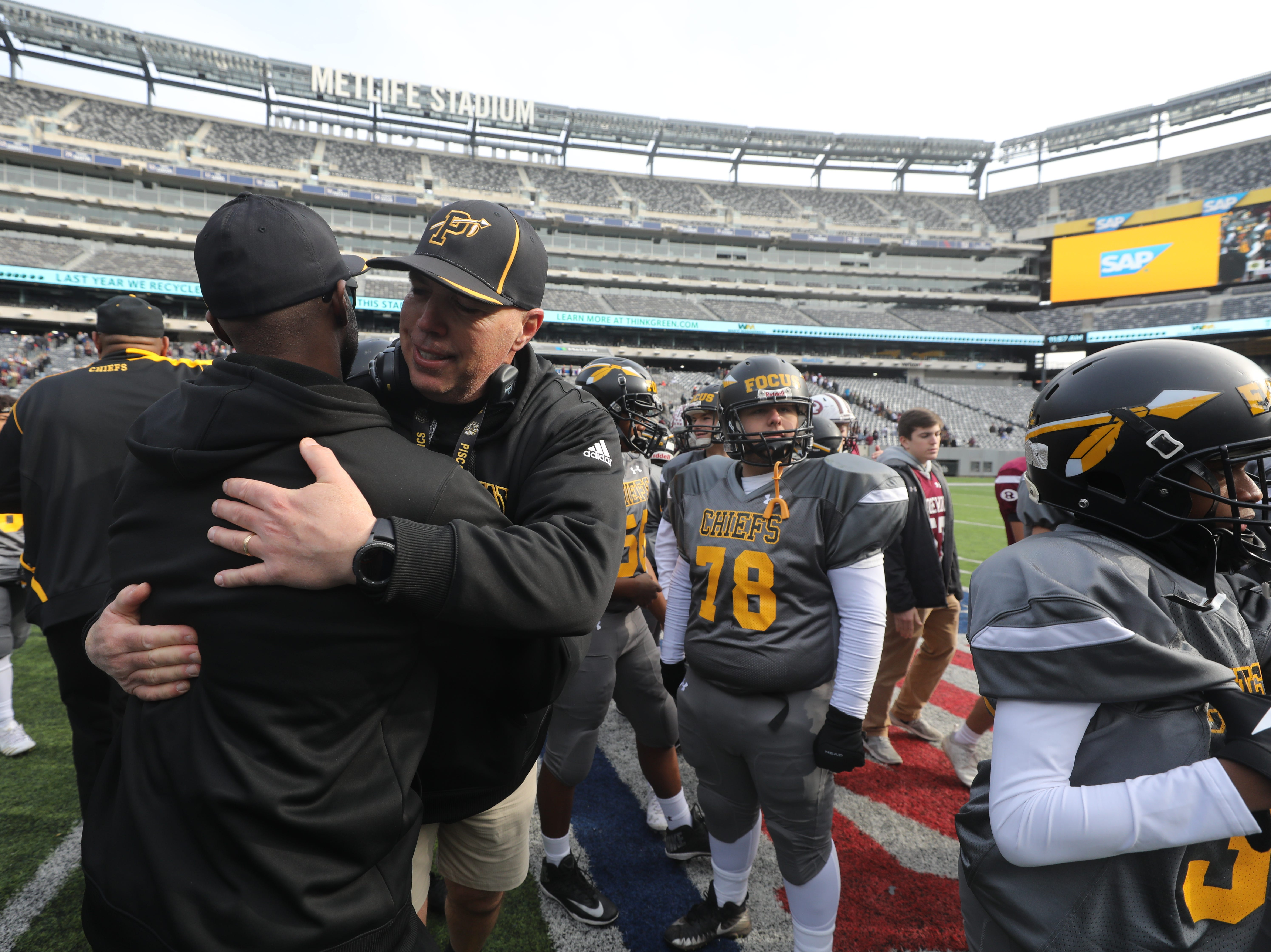 Piscataway head coach Daniel Higgins celebrates with his coaches at the end of the game.