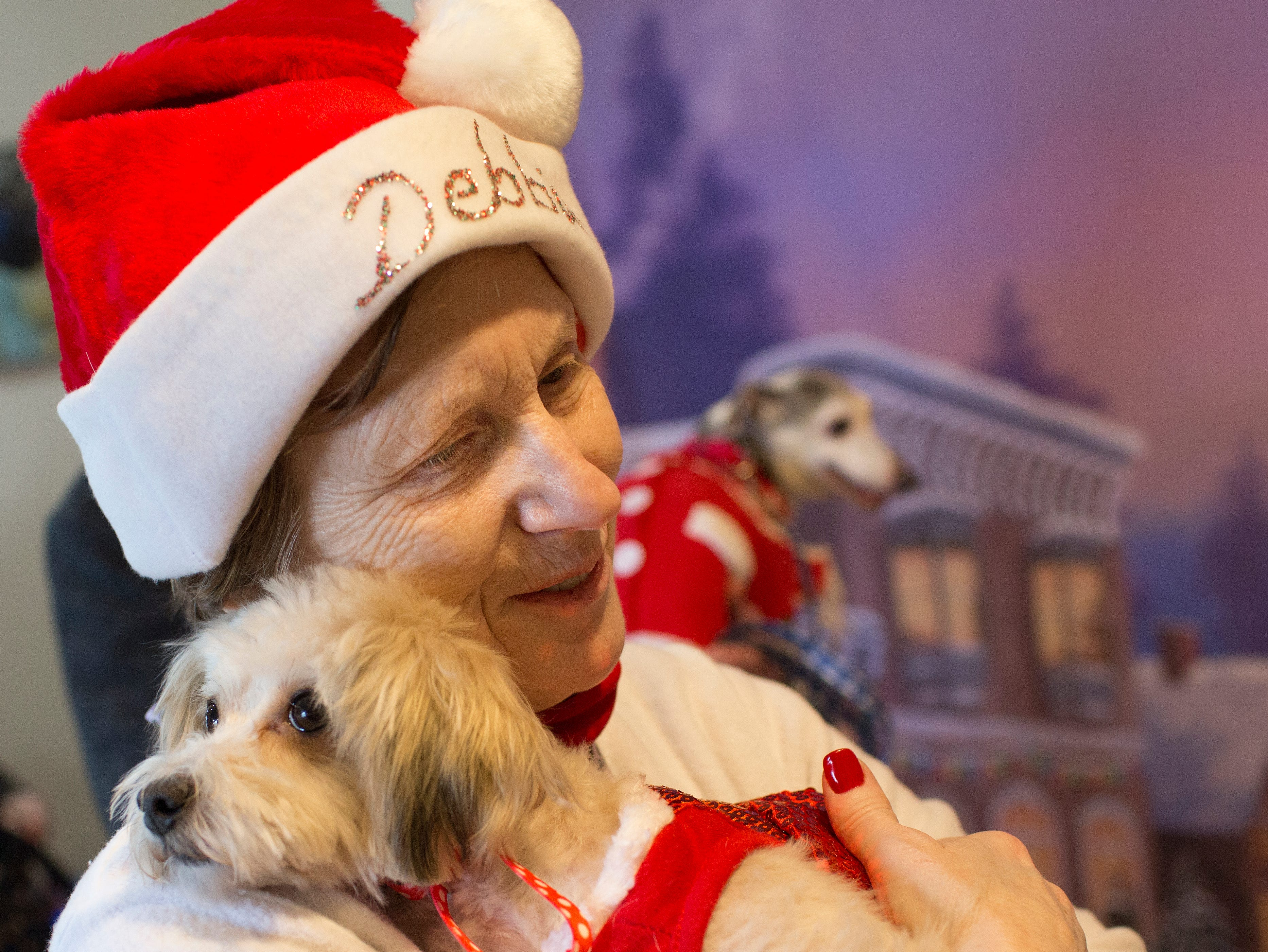 RBARI volunteer Debbie Zorbas holds Mandy, a four year old Poodle Maltese during the Santa Paws photo session for pets at the Rampo-Bergen Animal Refuge Inc. in Oakland on Saturday, Dec. 1, 2018. Sponsored by Allstate, all proceeds from the photo sessions go directly towards the care of animals rescued by RBARI.