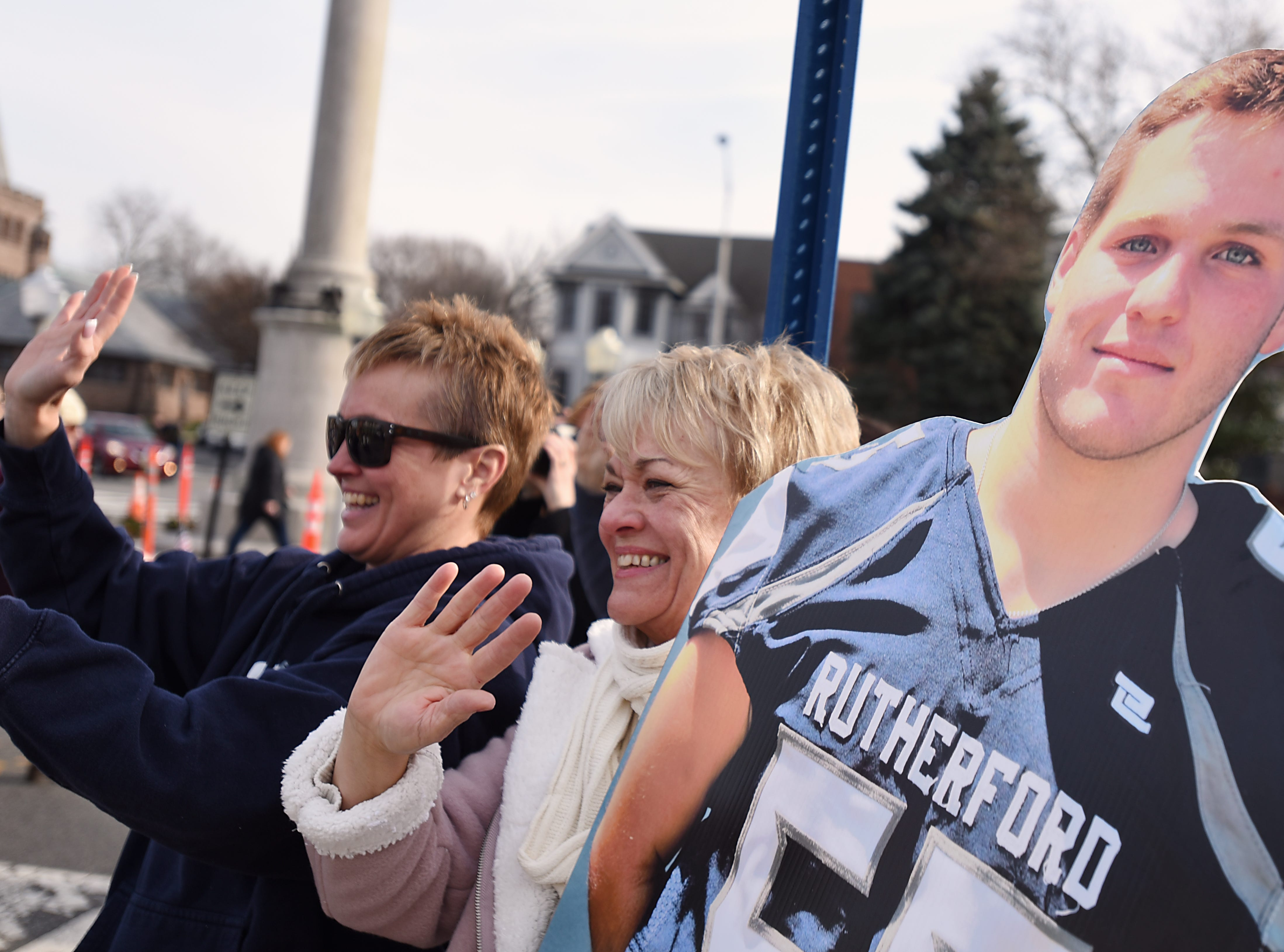 (From left) Cheryl Melfa and Cynthia Bott hold up a cut-out of Jack Melfa during the Rutherford Football parade in Rutherford on Saturday December 1, 2018.
