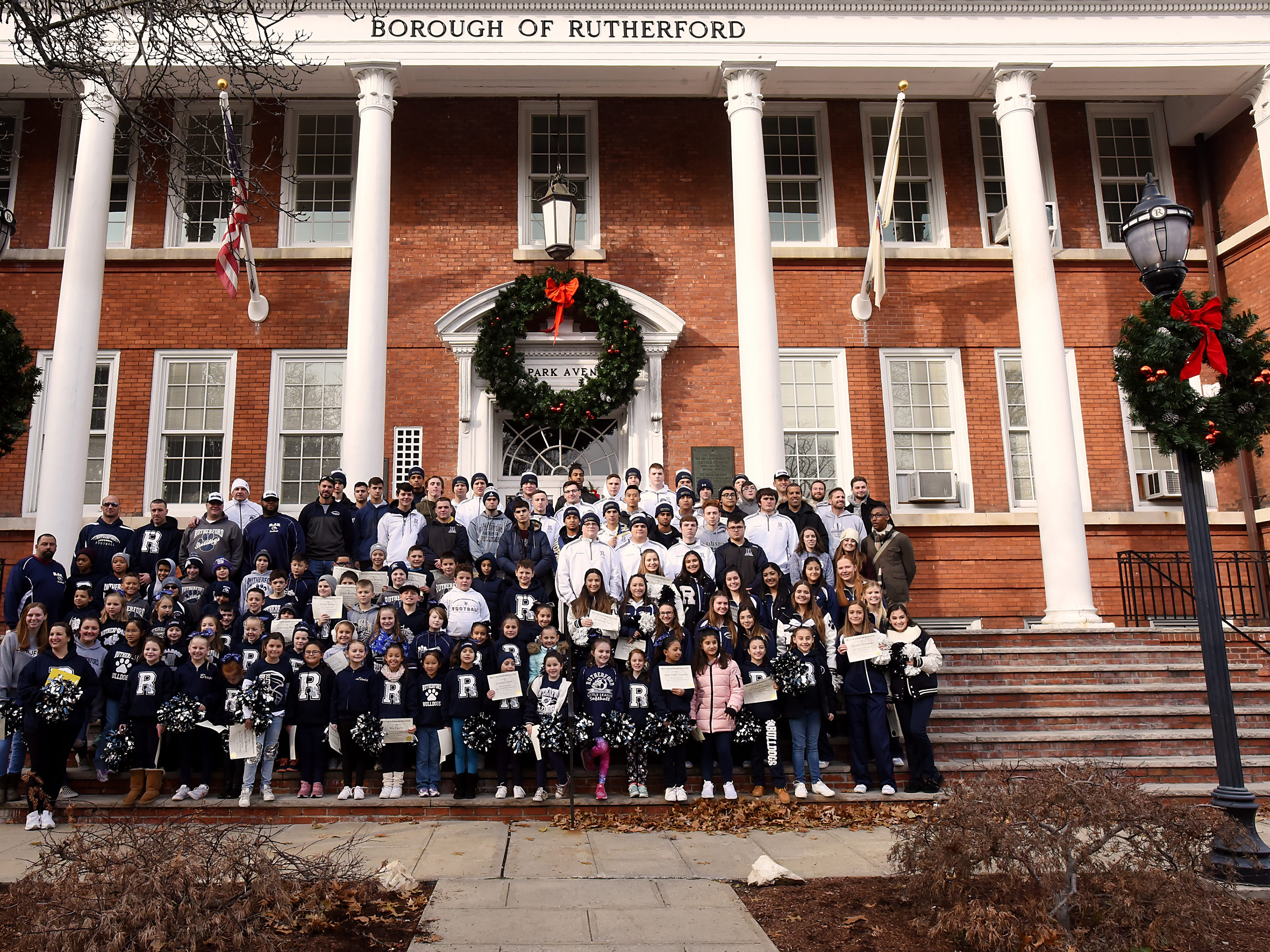 A group photo of the high school and peewee football and cheerleader teams after the Rutherford Football parade in front of the Rutherford Borough Hall on Saturday December 1, 2018.