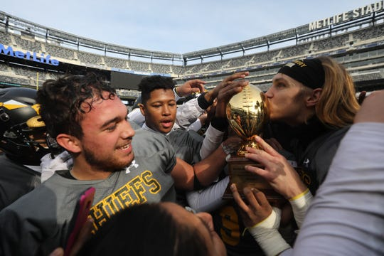 Nicholas Recine of Piscataway as team mate Joseph Hatcher kisses the trophy awarded to his team for being the North 1 Group 5 champions.
