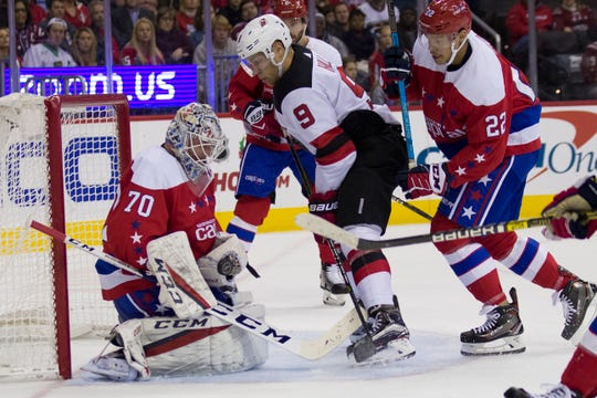 Washington Capitals goaltender Braden Holtby (70) blocks a shot by New Jersey Devils left wing Taylor Hall (9) with Capitals defenseman Madison Bowey (22) nearby during the second period of an NHL hockey game Friday, Nov. 30, 2018, in Washington.