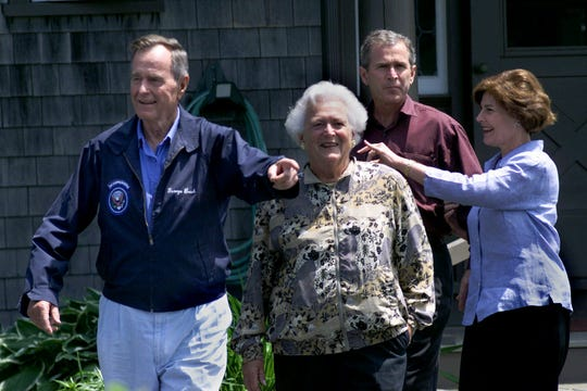 Former President George Bush, left, reacts to hundreds of journalists with wife Barbara, son Texas Gov George W. Bush with wife Laura at their family compound at Walker's Point in Kennebunkport, Maine, Sunday June 13, 1999.