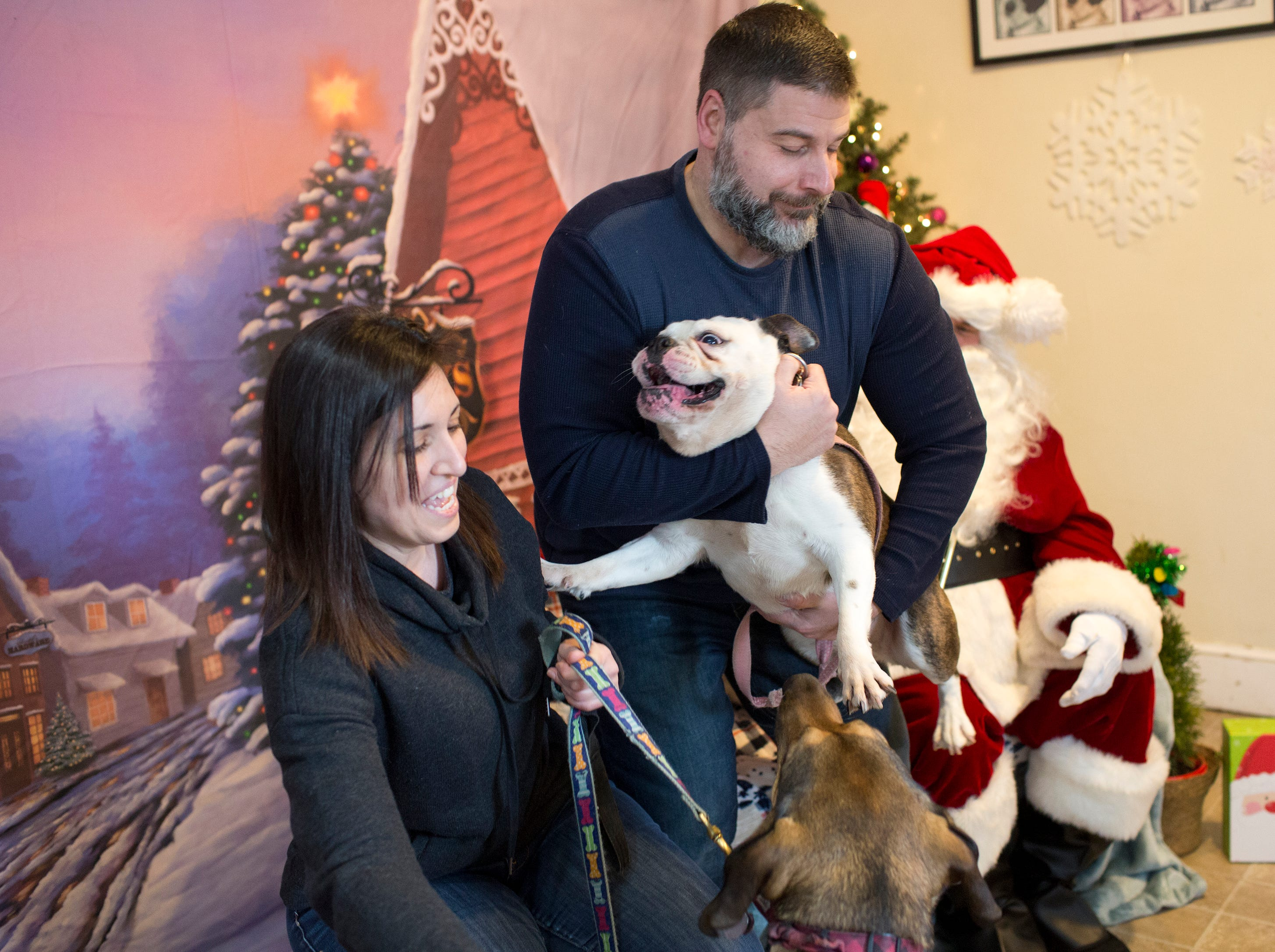 Al and Michelle Grambone of Wayne try to pose their dogs Harley (Bull dog) and Grayson, a German Shepherd, during the Santa Paws photo session for pets at the Rampo-Bergen Animal Refuge Inc. in Oakland on Saturday, Dec. 1, 2018. Sponsored by Allstate, all proceeds from the photo sessions go directly towards the care of animals rescued by RBARI.
