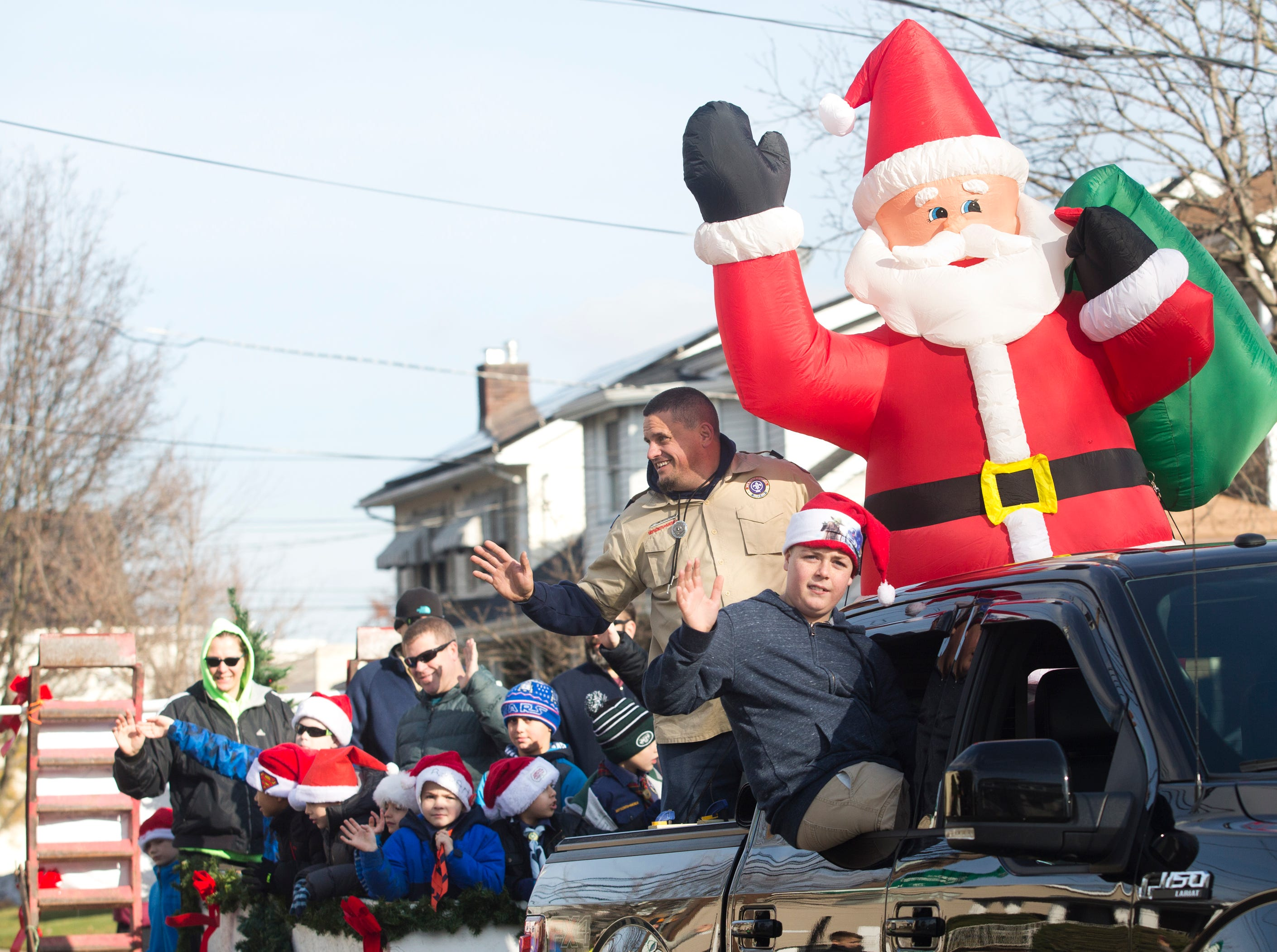St. Anthony's Cub Scout Pack of Hawthorne wave from their float during the 33rd Annual Santa Parade in Hawthorne on Saturday, Dec. 1, 2018.