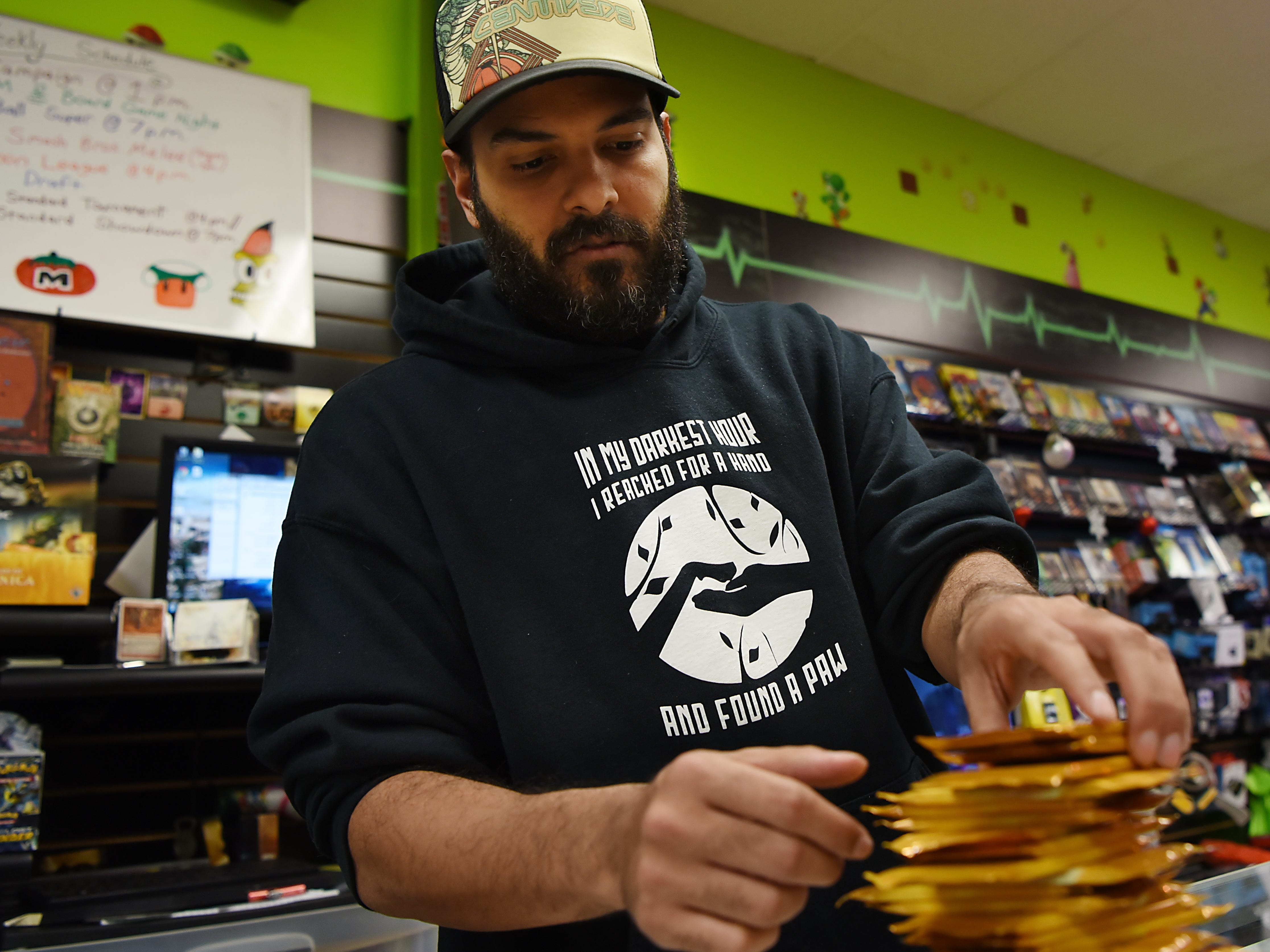 Emerito Rivera, the owner of Level 1 Games in Pompton Plains, arranges packs of Magic: The Gathering cards on Friday November 30, 2018.