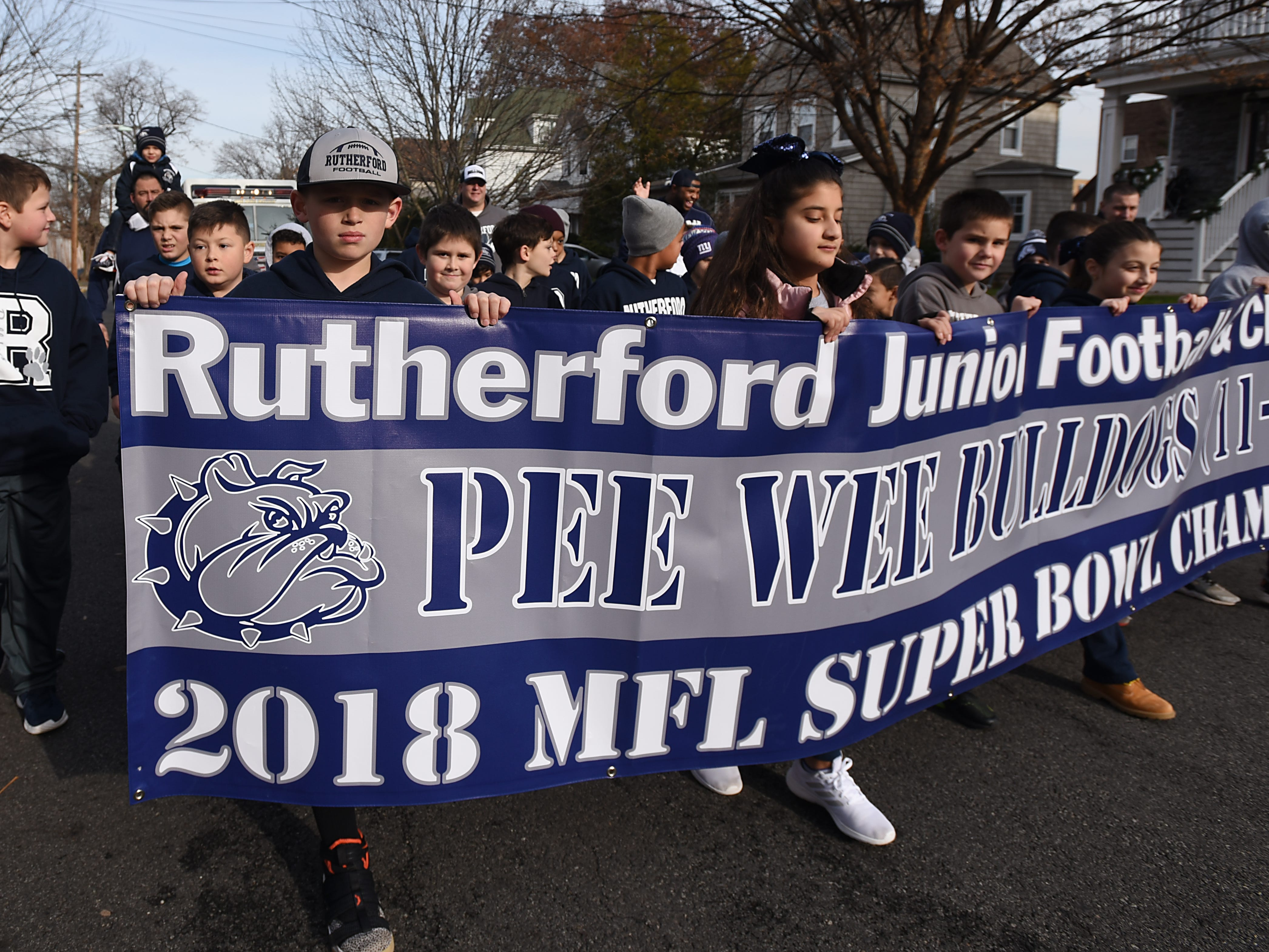 Cheerleaders and football players hold a banner during the Rutherford Football parade in Rutherford on Saturday December 1, 2018.