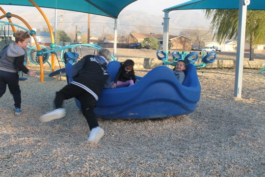Alamogordo children play on one to the many playground equipment at the new Kids' Zone at Indian Wells Road and Oregon Avenue Friday.