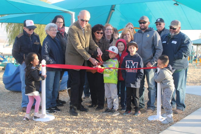 While getting help from a few youngsters and surrounded by city officials, Alamogordo Mayor Richard Boss cuts the ribbon at Kids' Zone to officially open the new playground Friday afternoon.