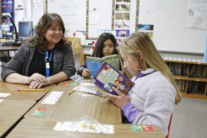 Cynthia Gustamantes, left, a third-grade teacher at McCoy Elementary School in Aztec, checks on Danica Oilyou, middle, and Emma Reidhead as they read Friday.