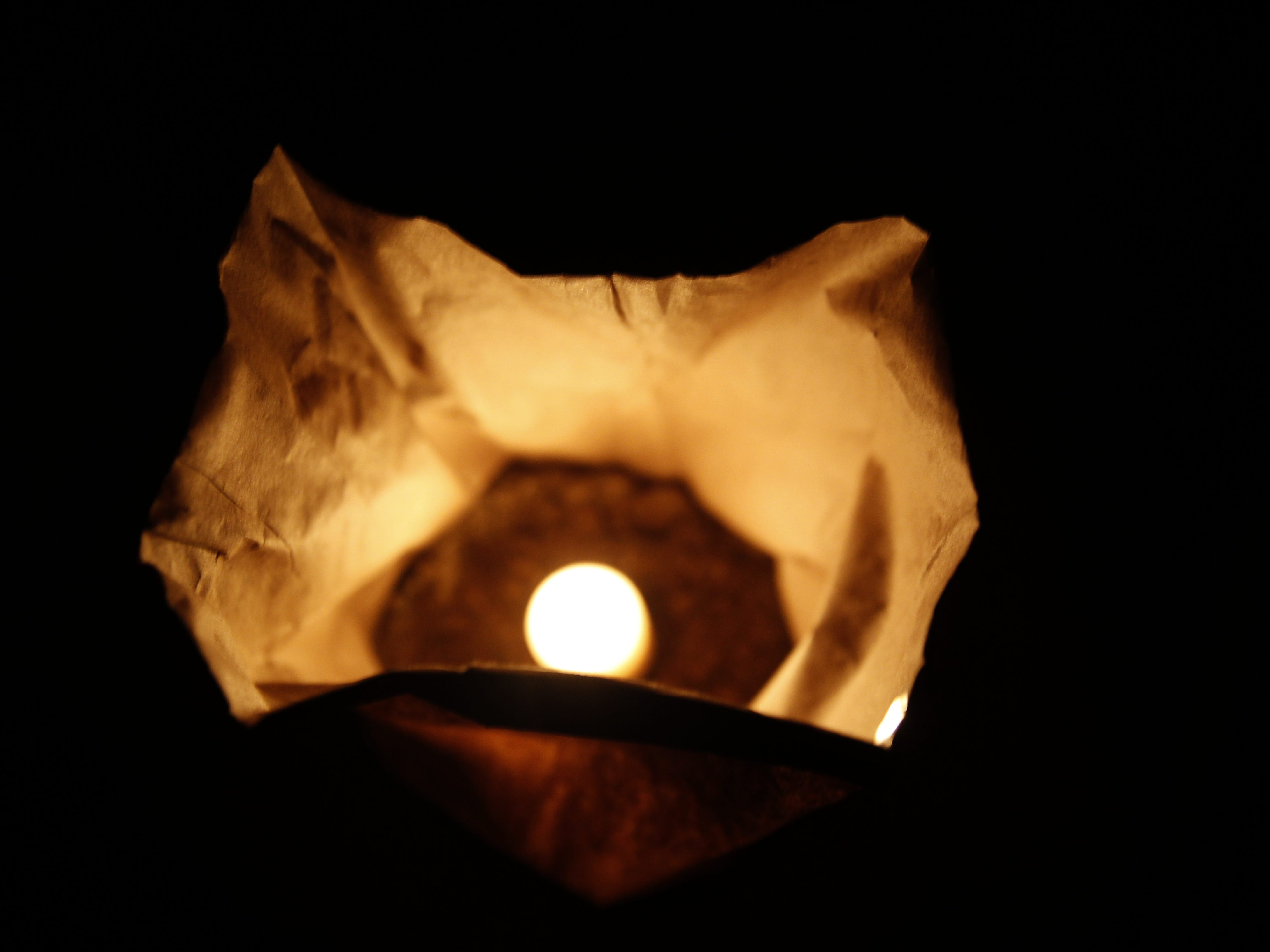 A candle burns in a luminaria bag, Friday, Nov. 30, 2018, during Riverglo in Berg Park in Farmington.