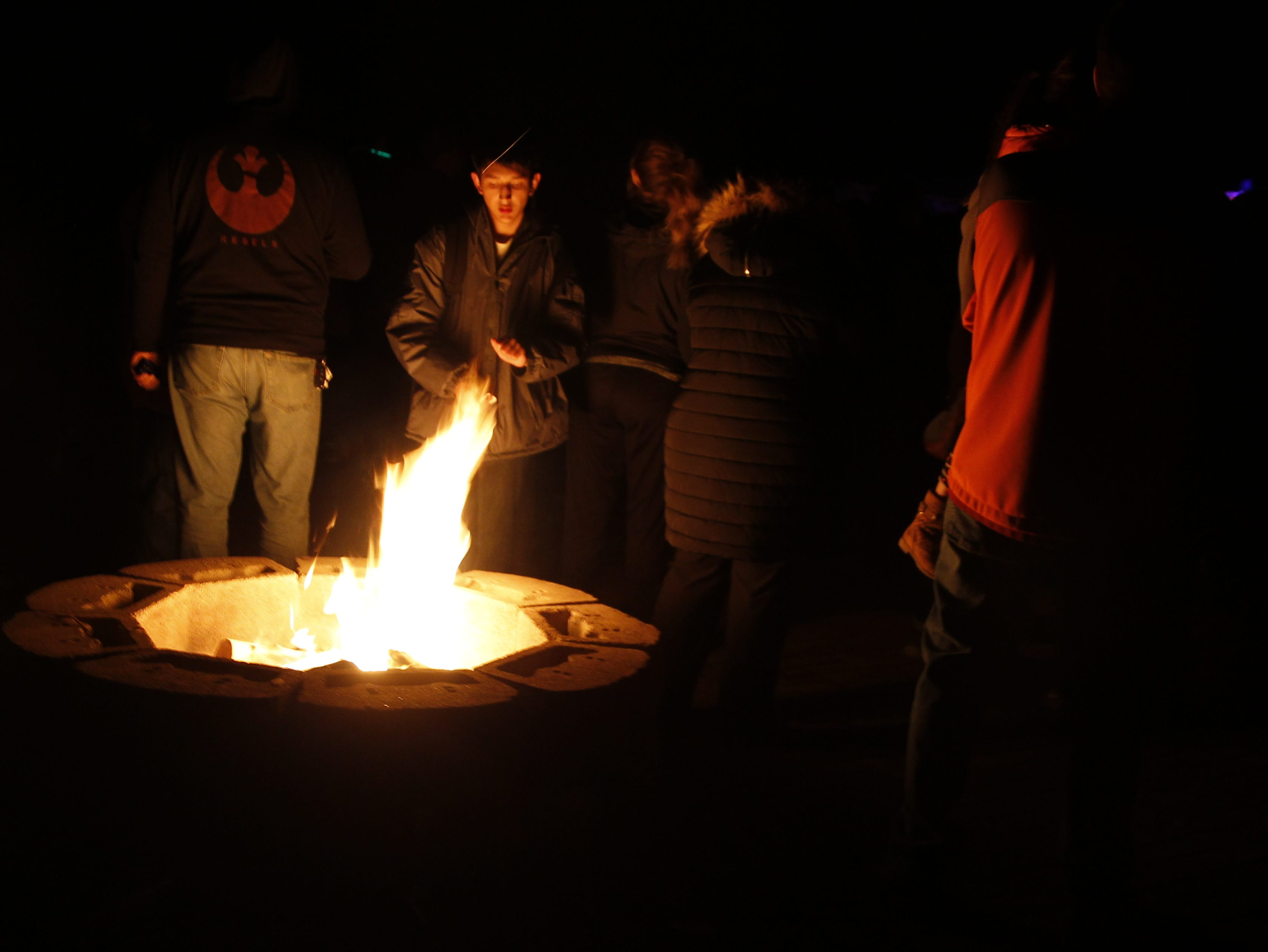 A crowd gathers around a fire, Friday, Nov. 30, 2018, during Riverglo in Berg Park in Farmington.
