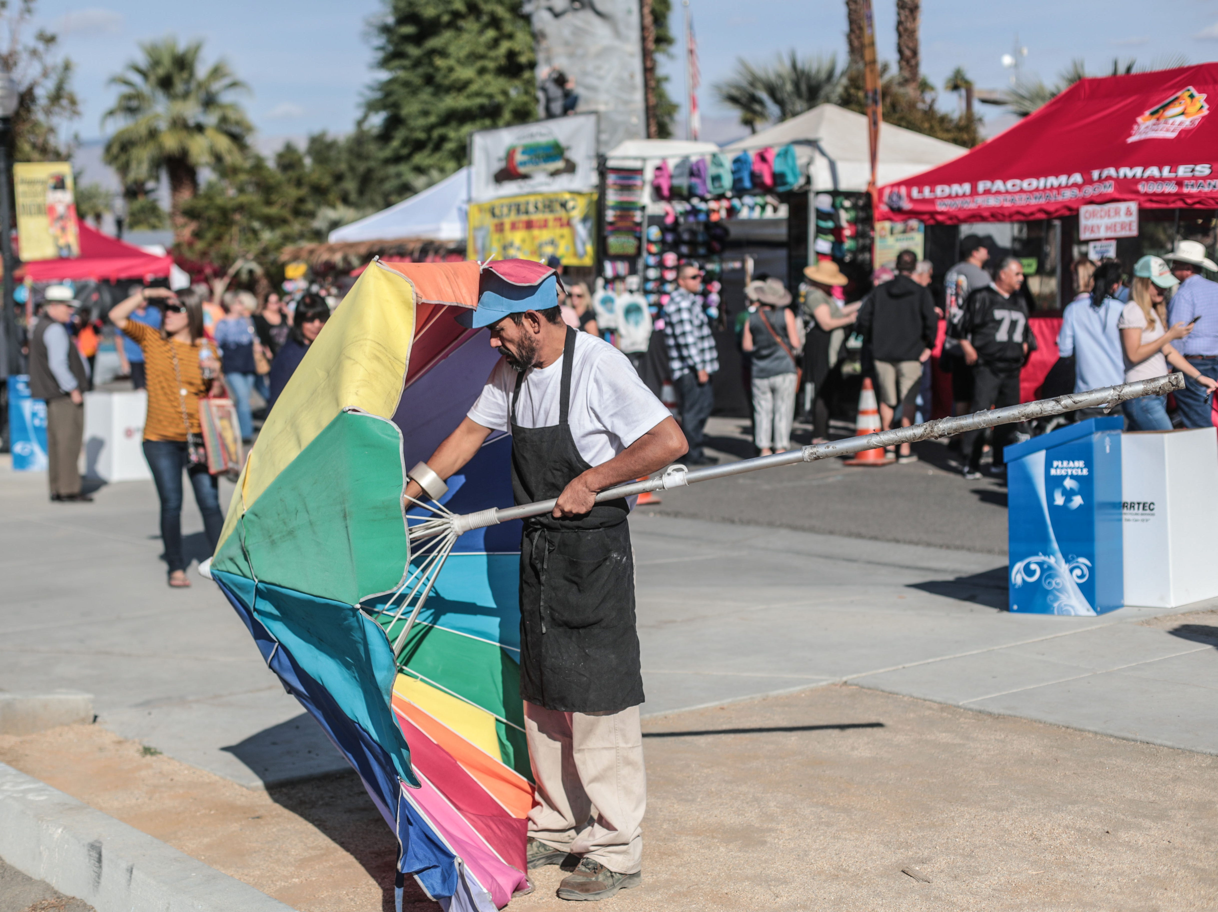 A man setting up an umbrella on Saturday, December 1, 2018 during annual Indio Tamales Festival.