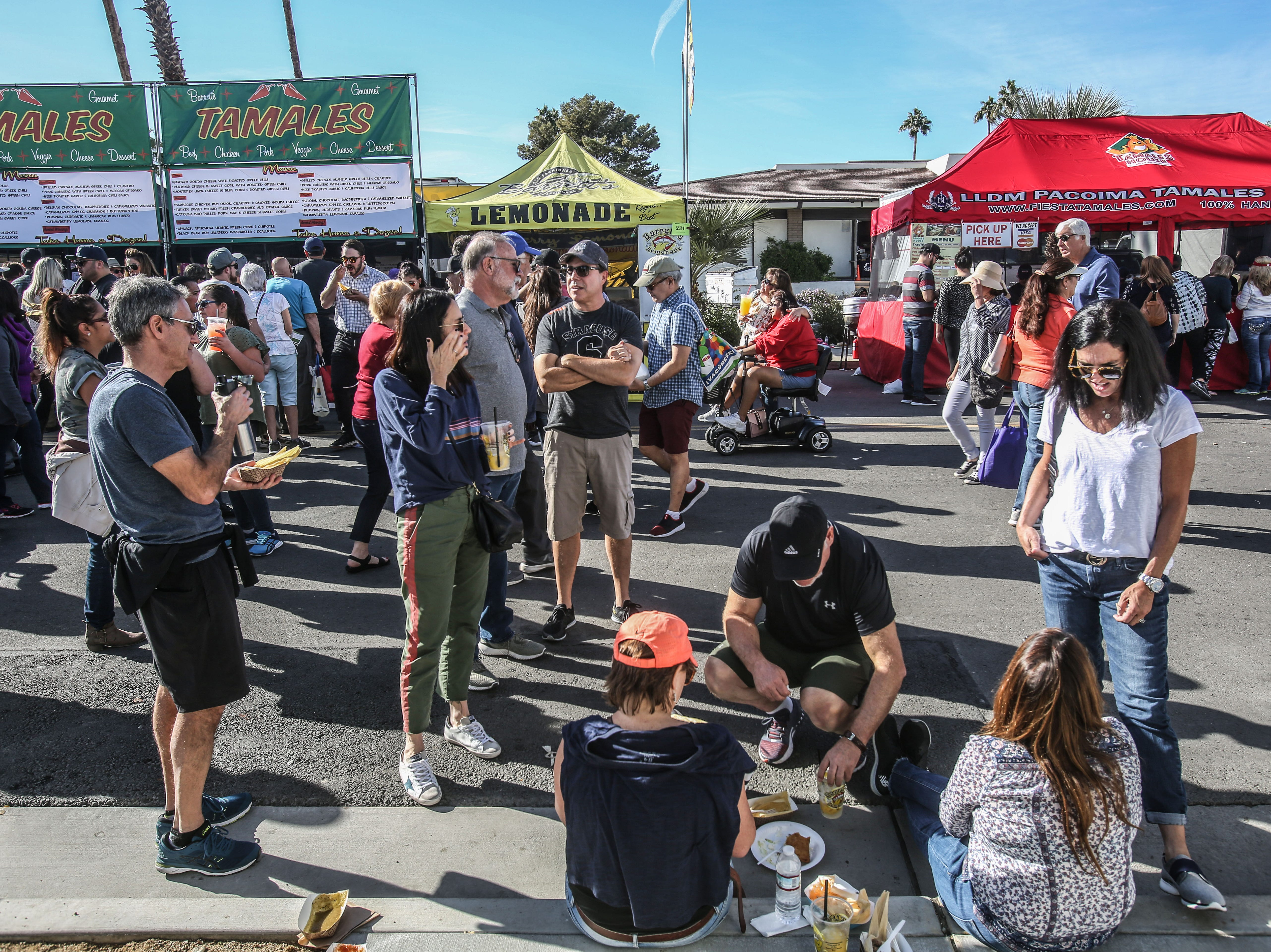 People eating tamales on the street on Saturday, December 1, 2018 during annual Indio Tamales Festival.