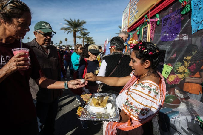 Isabel Martinez, 34, gives out tamale samples at the Tamales Escondido Tamaleria booth on Saturday, December 1, 2018 during annual Indio Tamales Festival.