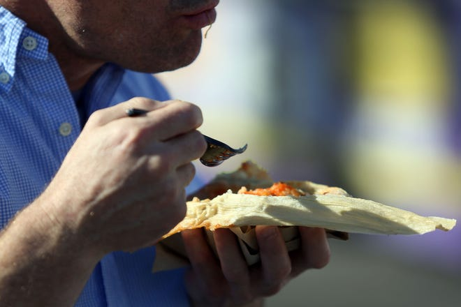 A man eats his tamale on Saturday, December 1, 2018 during annual Indio Tamales Festival.