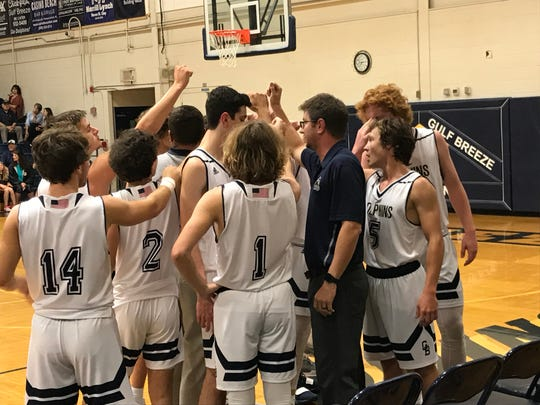 Gulf Breeze High boys basketball coach Ryan Ottensmeyer, (blue shirt) and his Dolphins team are off to a solid start, following Friday's 74-69 win against Lynn Haven-Mosley.
