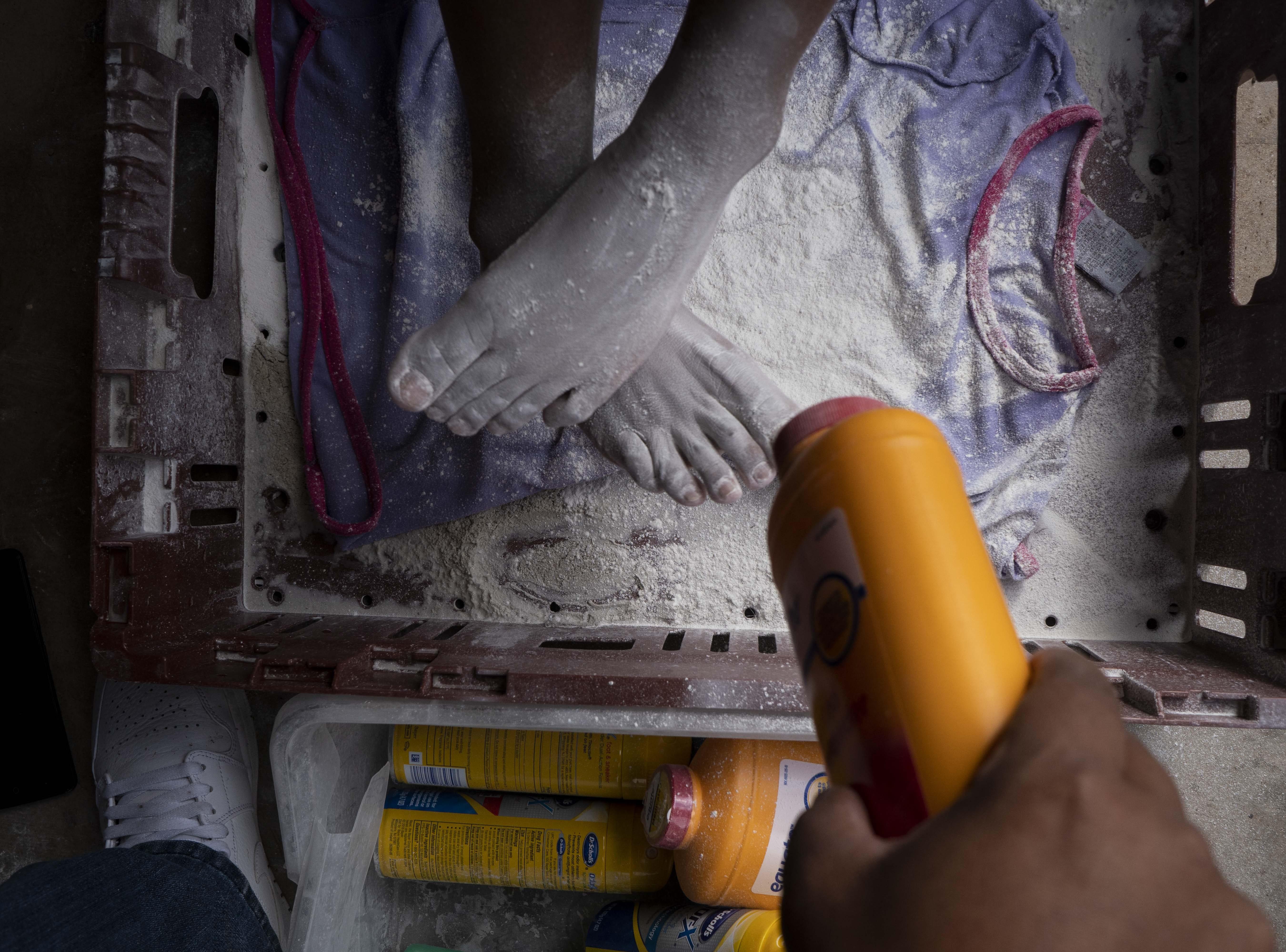 Church volunteers help migrants clean their feet.