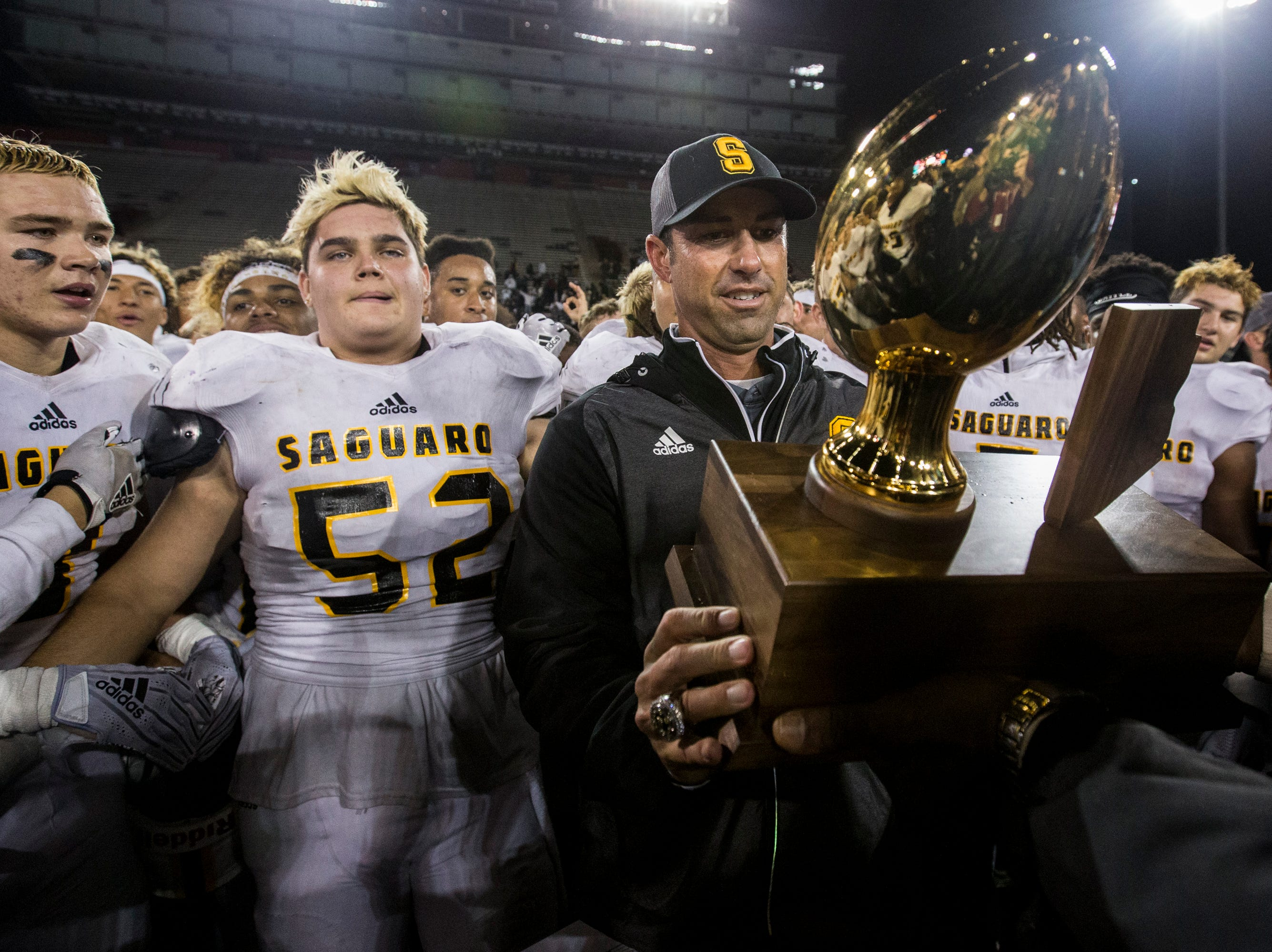 Saguaro head coach Jason Mohns accepts the trophy after defeating Salpointe for the 4A State Championship on Friday, Nov. 30, 2018, at Arizona Stadium in Tucson, Ariz. Saguaro won, 42-16.