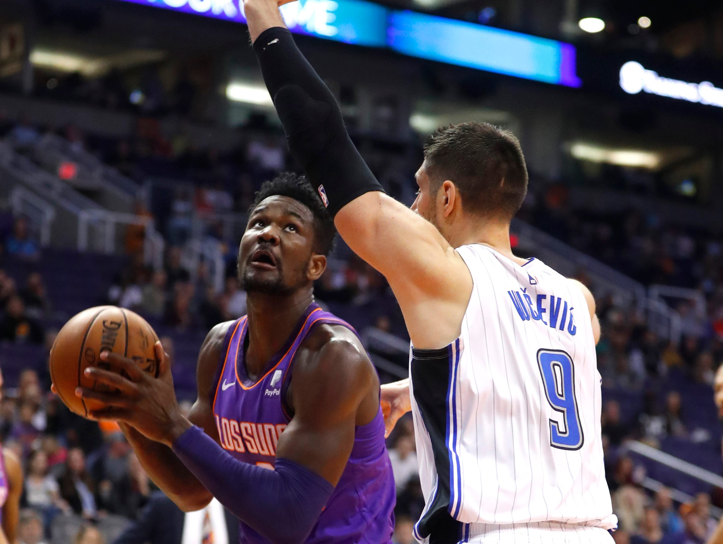 Suns' Deandre Ayton (22) goes up for a shot against Magic's Nikola Vucevic (9) during the first half at Talking Stick Resort Arena in Phoenix, Ariz. on November 30, 2018.
