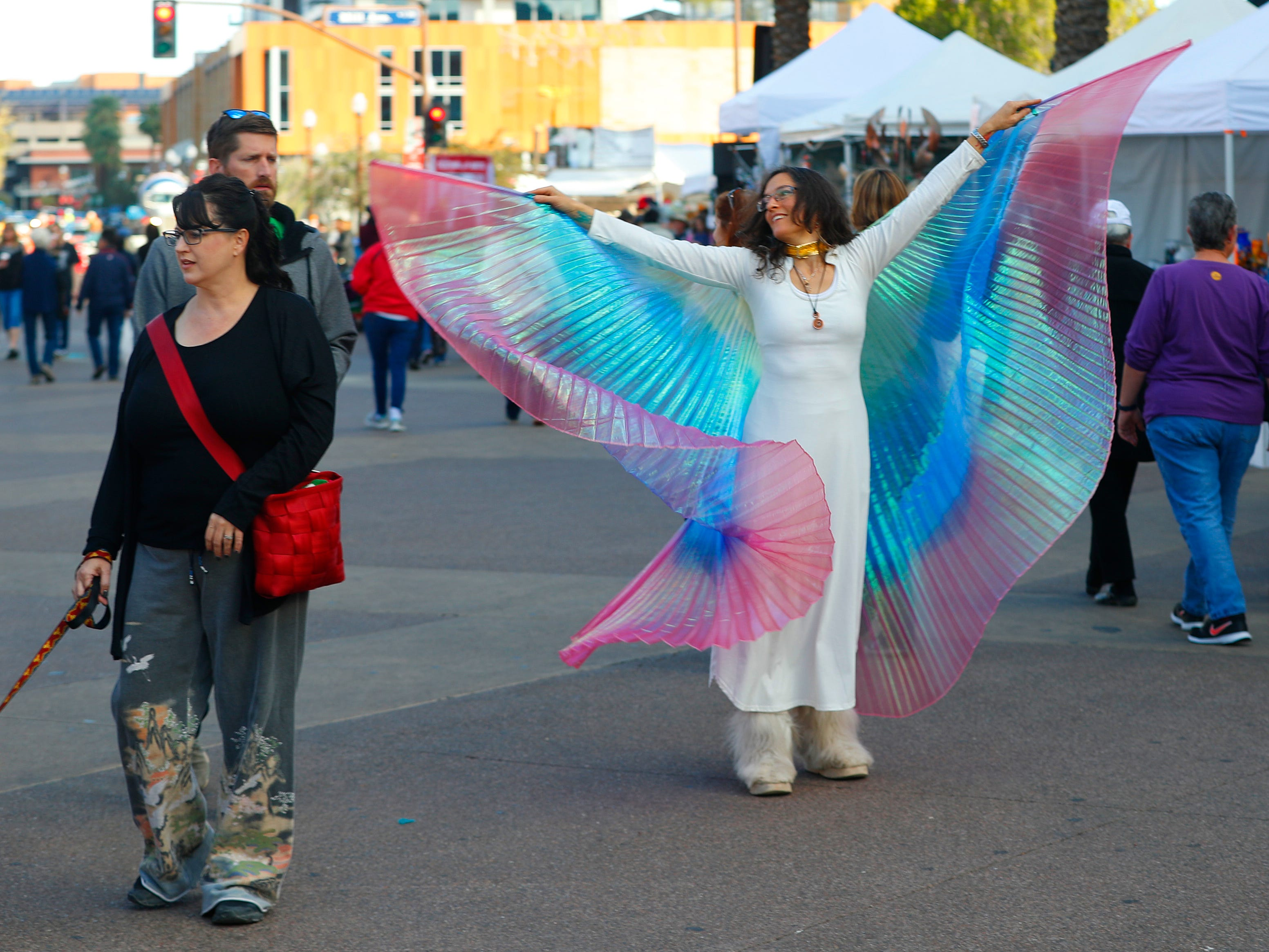 Rachel Mari Kimber dances with her wings at the Tempe Festival of the Arts on Mill Avenue on Friday, November 30, 2018.