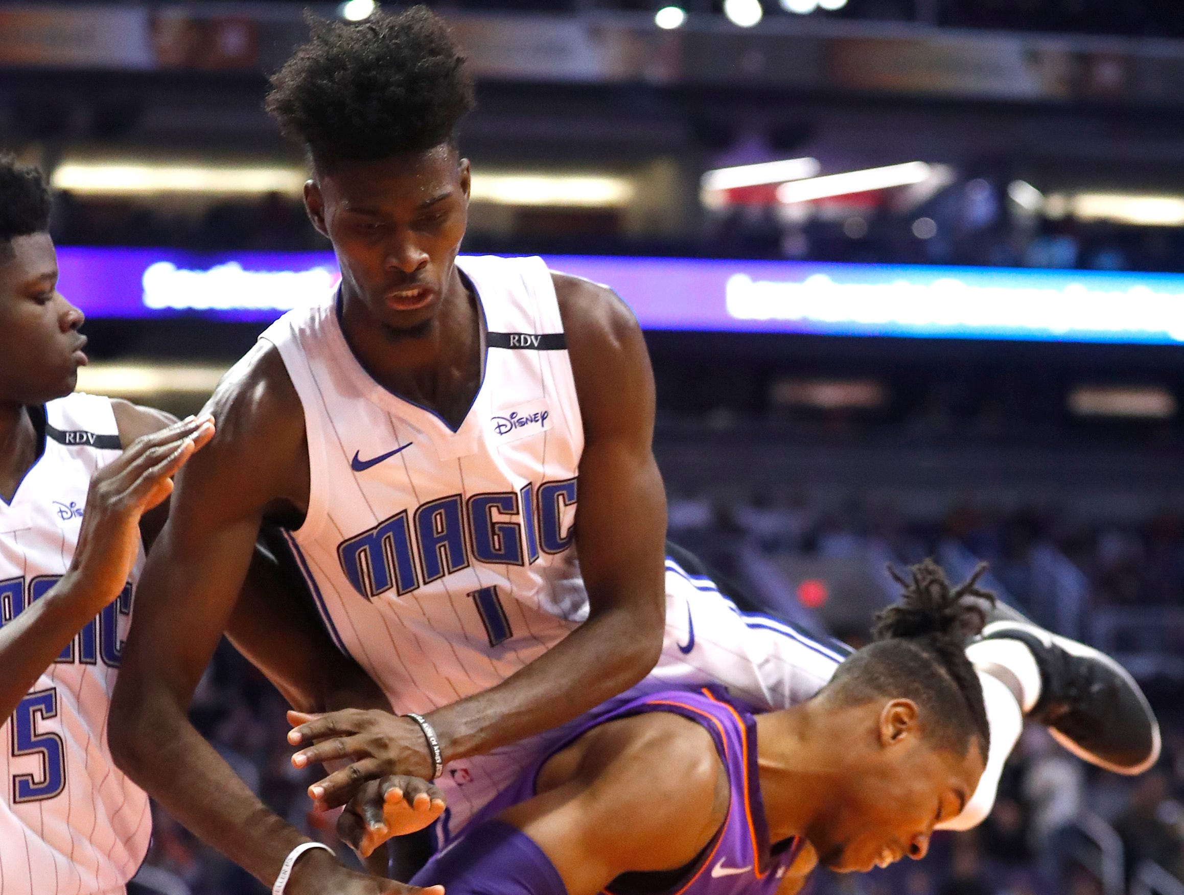 Magic's Jonathan Isaac (1) jumps on the back of Suns' Richaun Holmes (21) for a foul during the first half at Talking Stick Resort Arena in Phoenix, Ariz. on November 30, 2018.