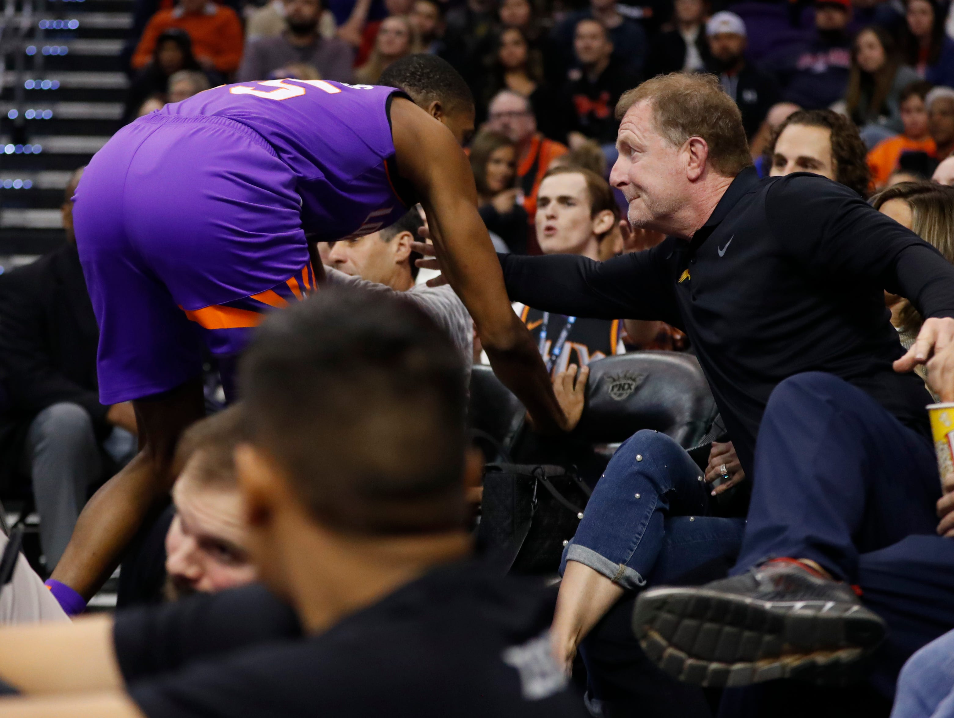 Suns' owner Robert Sarver puts an arm out to grab Suns' forward Mikal Bridges (15) as he dove into the fans for a loose ball against the Magic during the first half at Talking Stick Resort Arena in Phoenix, Ariz. on November 30, 2018.