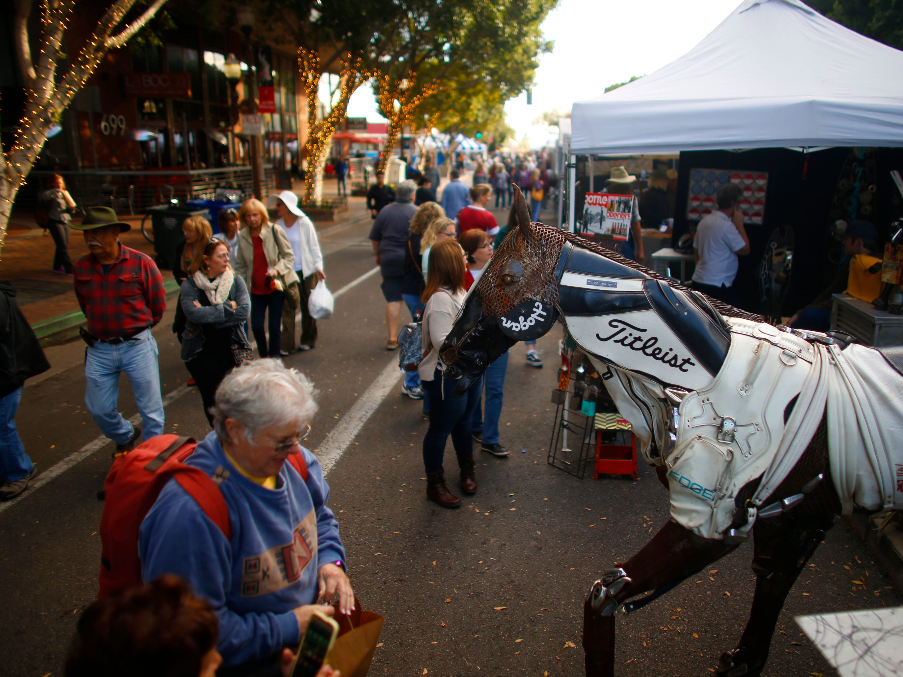 People make their way around the local artists and their shops at the Tempe Festival of the Arts on Mill Avenue on Friday, November 30, 2018.