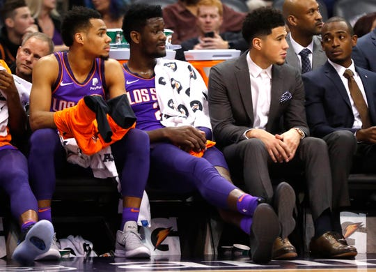 Suns' Elie Okobo (L-R) Deandre Ayton and Devin Booker watch the game against the Magic from the bench during the first half at Talking Stick Resort Arena in Phoenix, Ariz. on November 30, 2018.