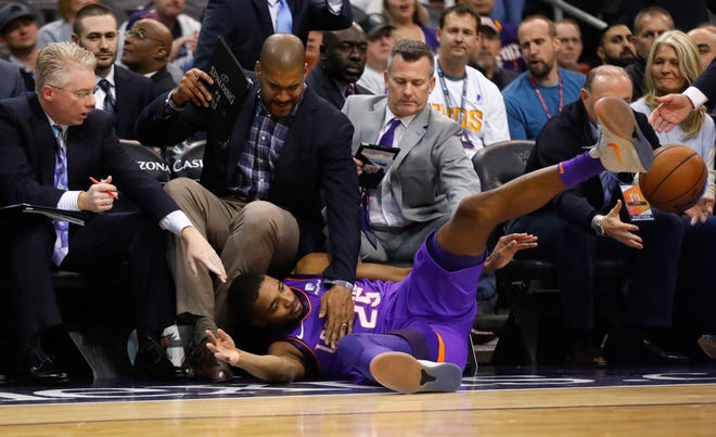 Suns' Mikal Bridges (25) dives into the coaches trying to save a loose ball against the Magic during the first half at Talking Stick Resort Arena in Phoenix, Ariz. on November 30, 2018.
