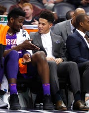 Suns' Deandre Ayton and Devin Booker talk about his suit on the bench during the first half at Talking Stick Resort Arena in Phoenix, Ariz. on November 30, 2018.