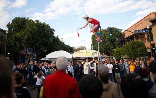 The unicycling unicorn, Jamey Mossengren, performs for the crowds at the Tempe Festival of the Arts on Mill Avenue on Friday, November 30, 2018.