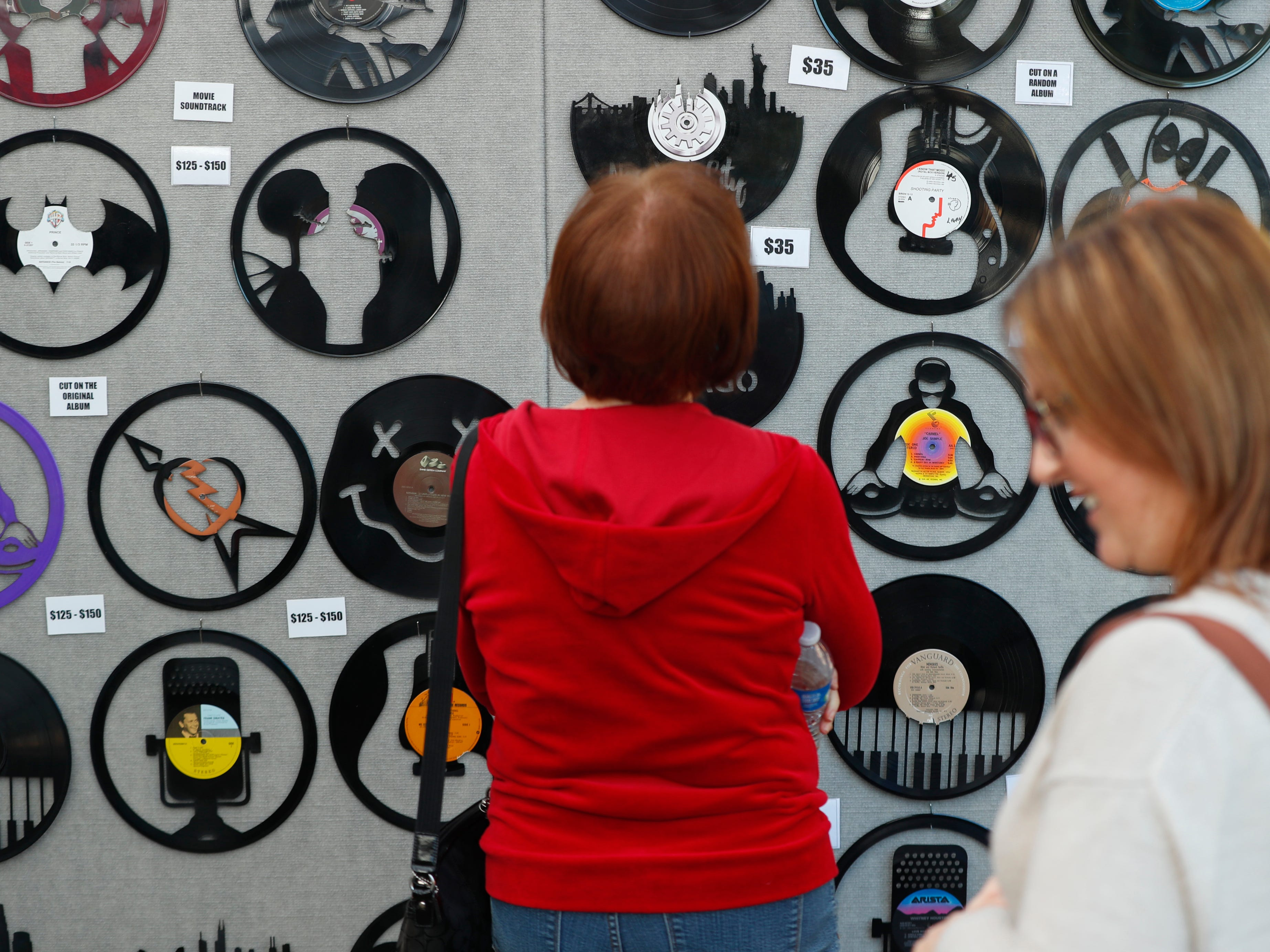 People look over record art designed by Alex Grimmer at the Tempe Festival of the Arts on Mill Avenue onFriday, November 30, 2018.
