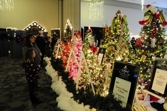 People admire decorated trees at the Festival of Trees on Saturday, Dec. 1, 2018 at the Blue Water Convention Center.