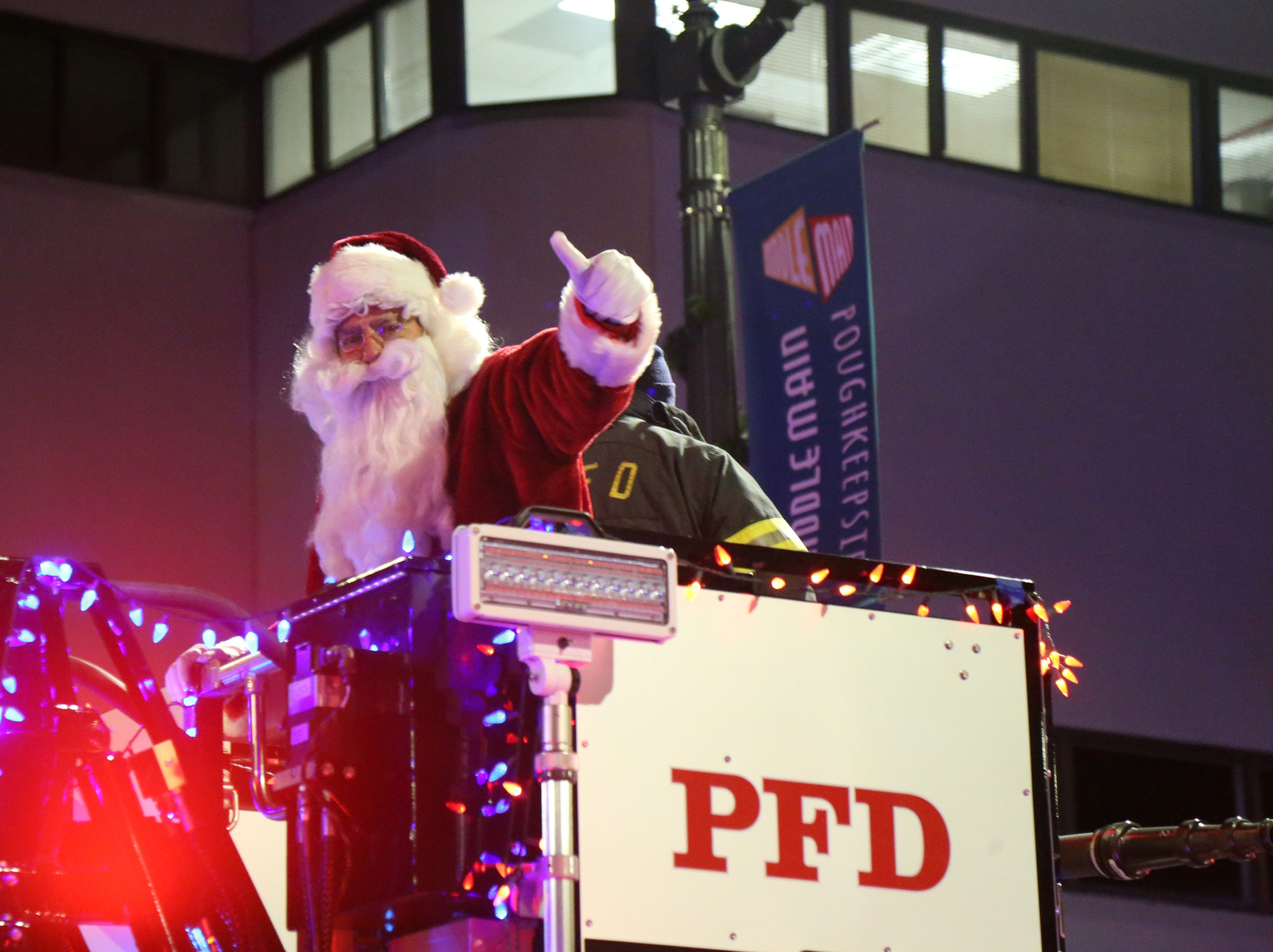 Santa Claus rides on a City of Poughkeepsie fire truck during the Celebration of Lights in the City of Poughkeepsie on November 30, 2018.