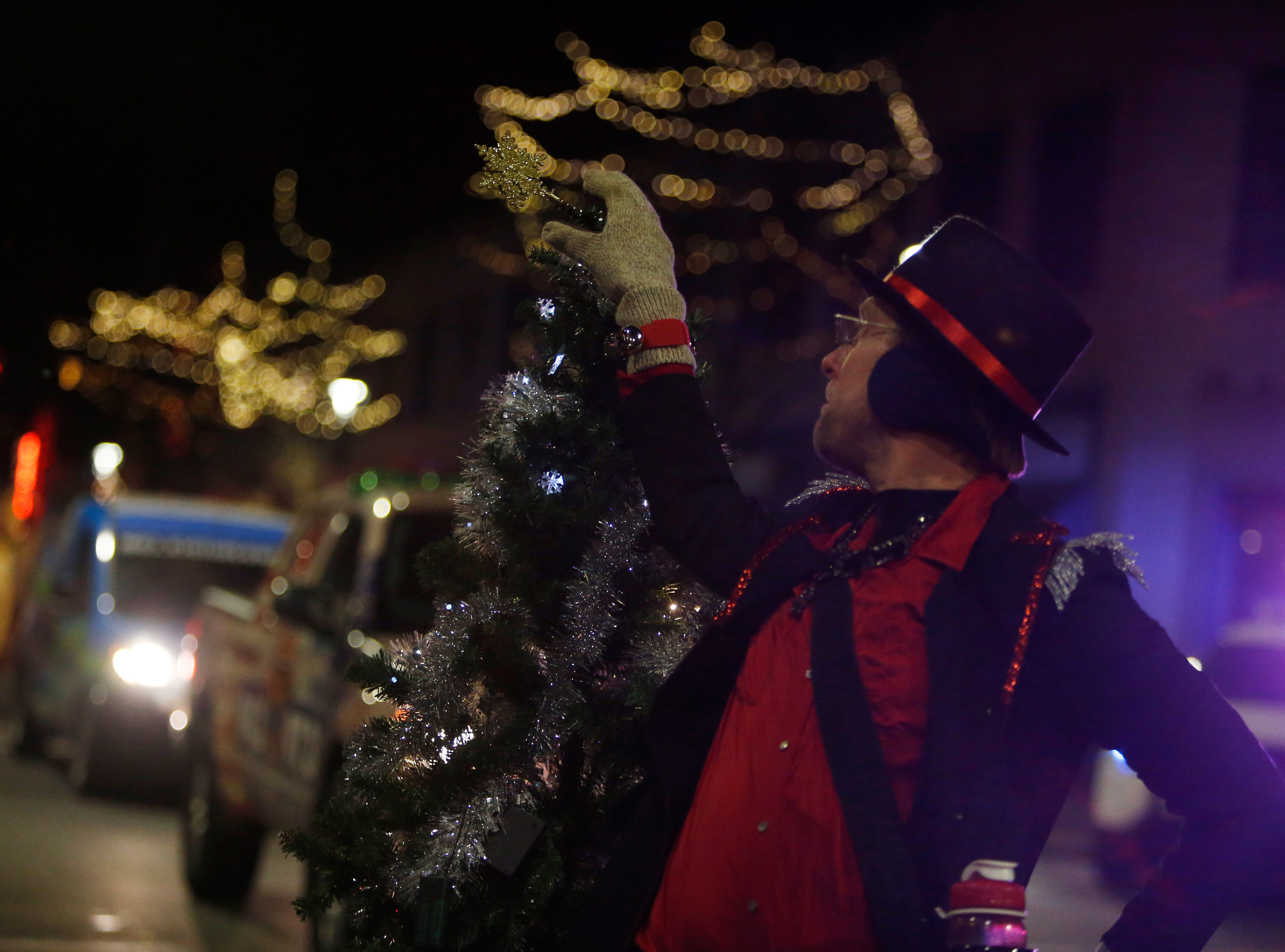 Frank Richards from of Fats in the Cats Bicycle Club adjusts the top to his bicycle's Christmas Tree during the Celebration of Lights Parade in the City of Poughkeepsie on November 30, 2018.