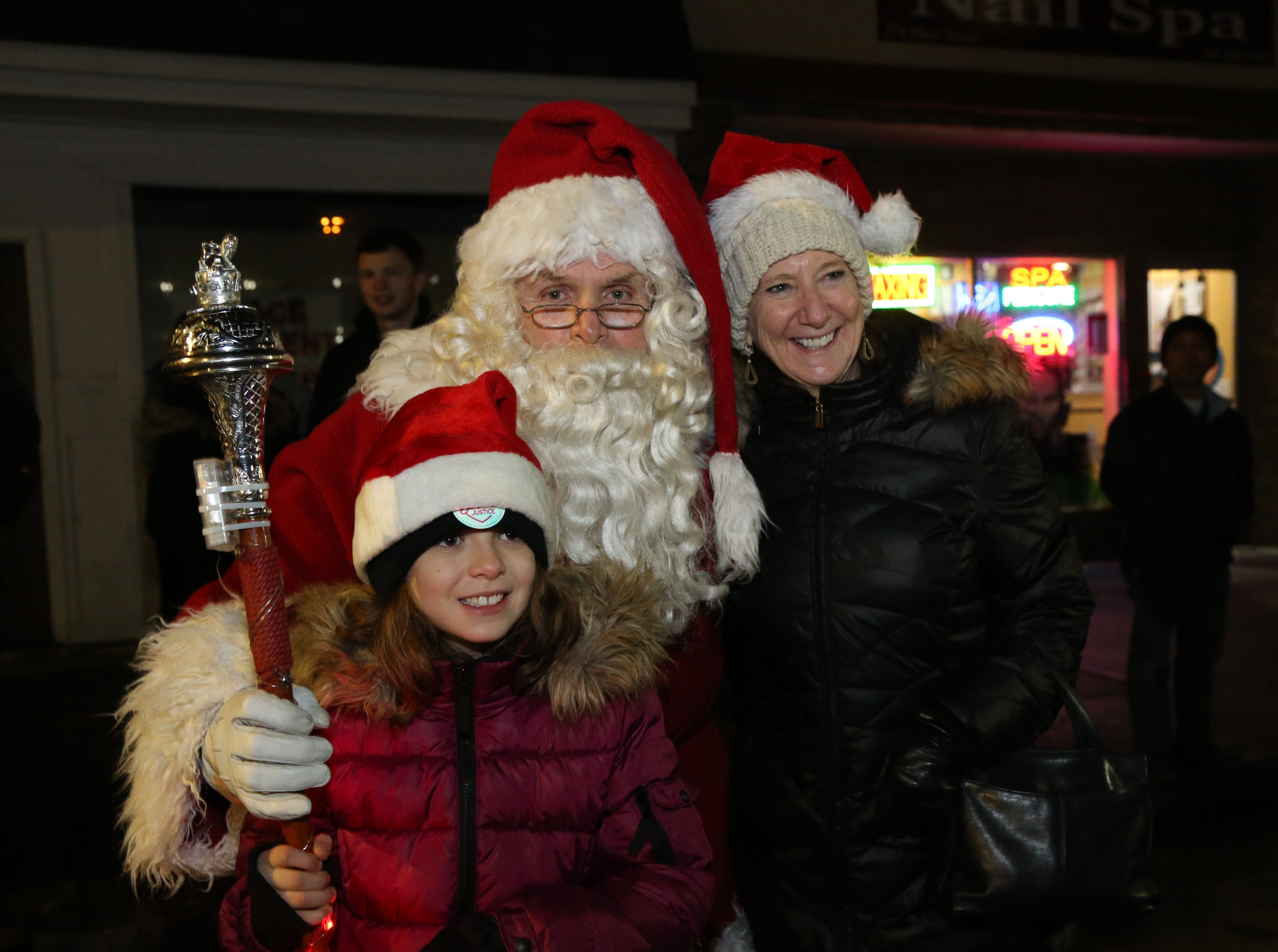 Linda McAvoy with her granddaughter Michaela pose with Santa Claus,  Amerscot Highland Pipe Band's Bill Tompkins during the Celebration of Lights Parade in the City of Poughkeepsie on November 30, 2018.