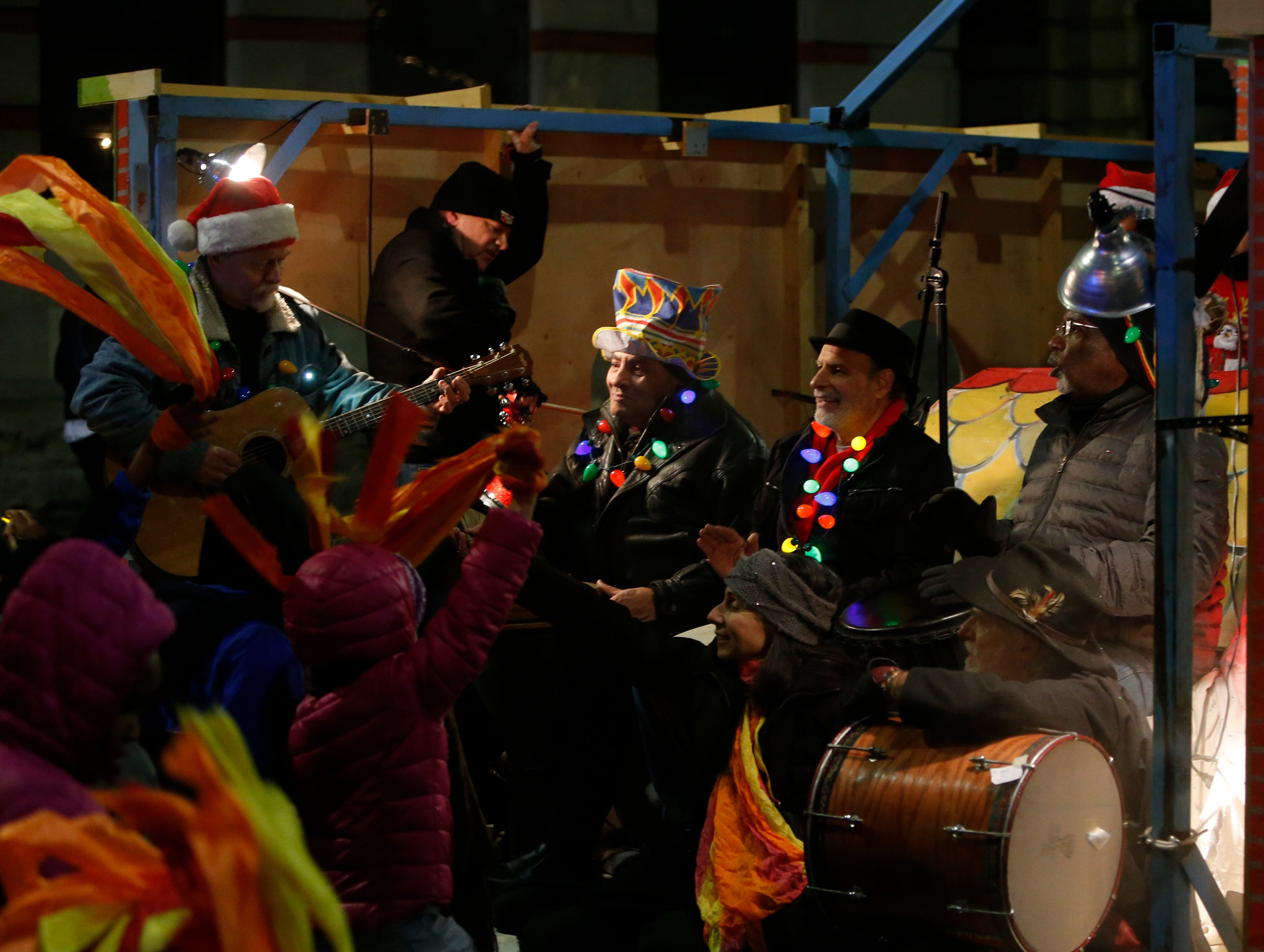 From left, David Hennisen, Aldin Chiappolini, Franc Palaia and Bryan Henry play music on the back of the Cuneen Hackett Arts Center float during the Celebration of Lights in the City of Poughkeepsie on November 30, 2018.