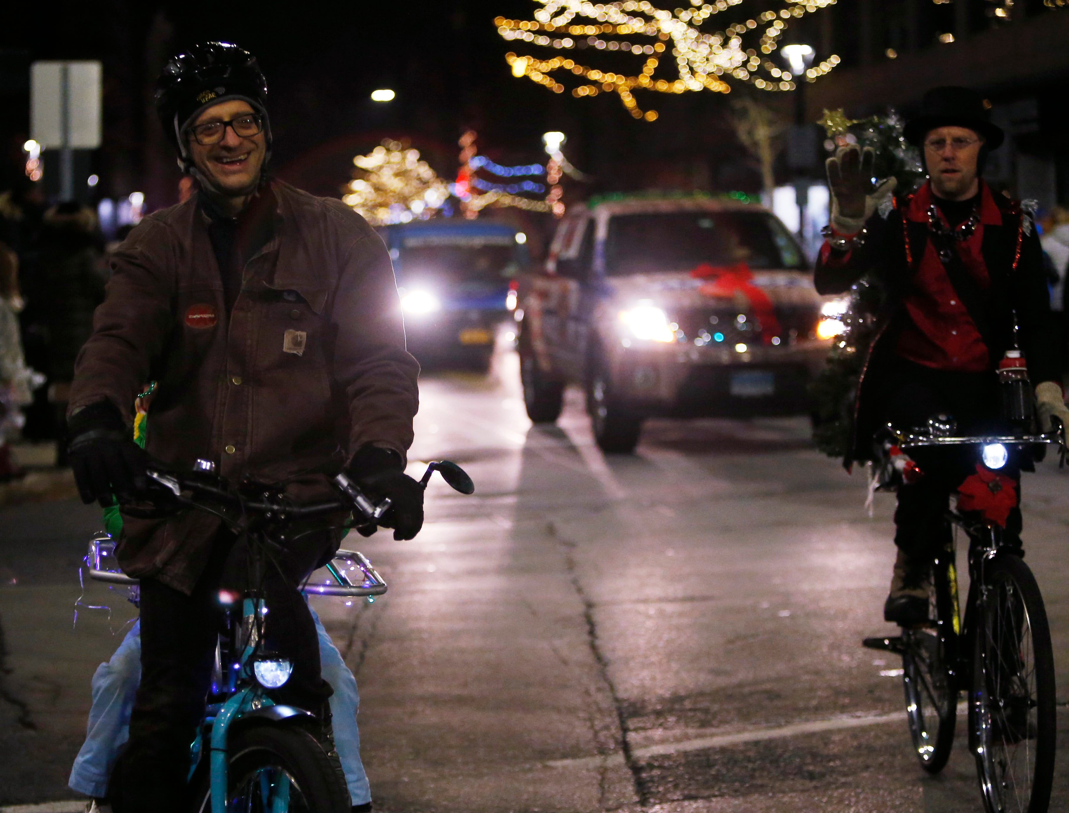 From left, Johnny Galbraith and Frank Richarts pedal in the Celebration of Lights Parade in the City of Poughkeepsie on November 30, 2018.