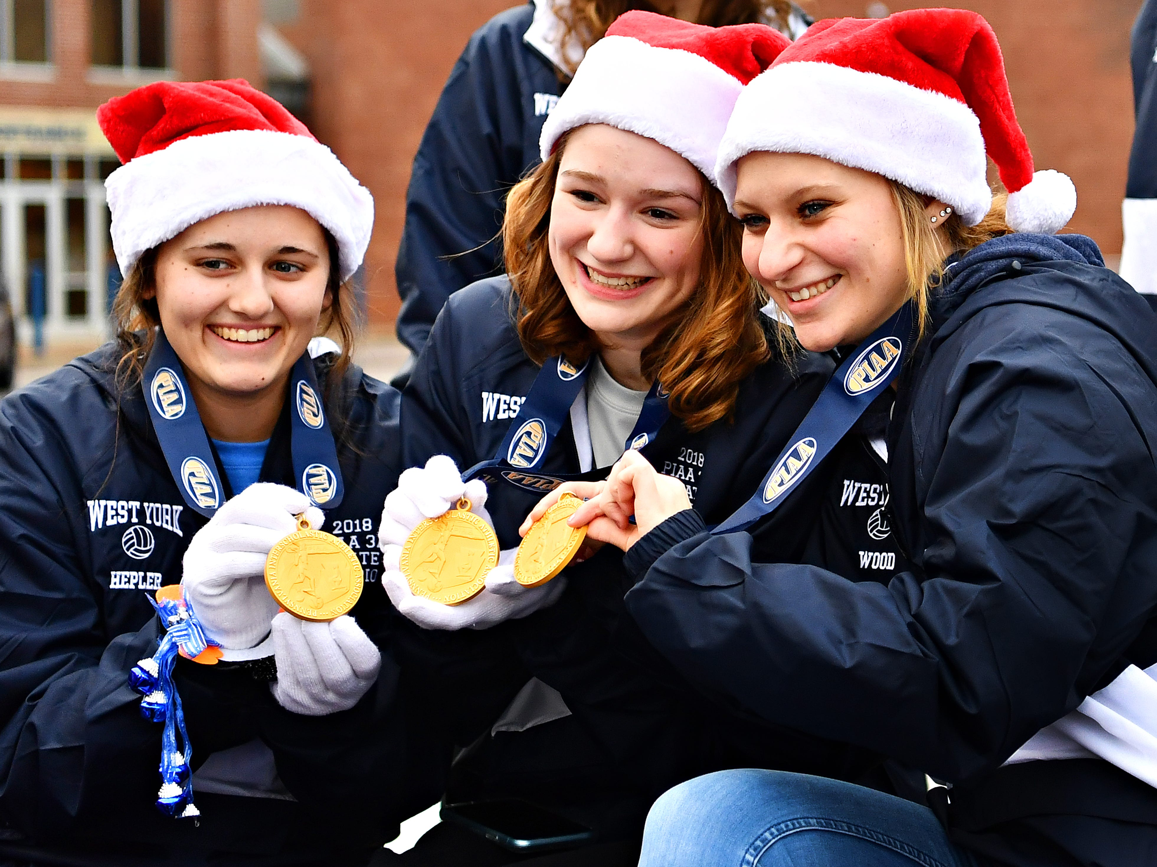 From left, West York's Kambrie Hepler, Julia Rill and Lizzie Wood show their championship medals to media prior to the the parade honoring the 2018 PIAA 3-A State Champion Lady Bulldogs Volleyball team at West York Area High School in West Manchester Township, Friday, Nov. 30, 2018. Dawn J. Sagert photo